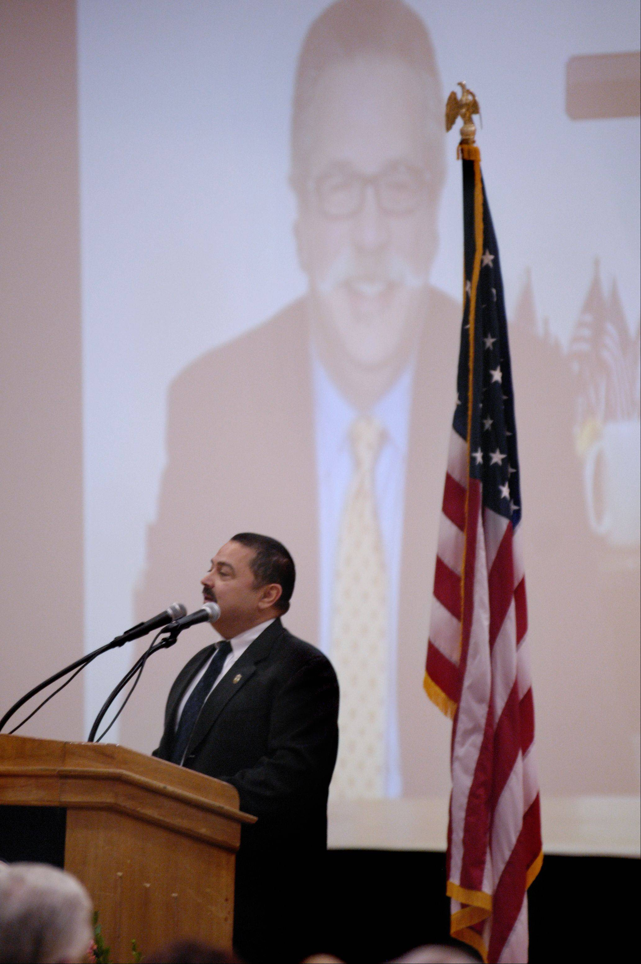 Alderman and friend Ruben Pineda speaks Sunday at the memorial service for West Chicago Mayor Mike Kwasman at West Chicago High School.