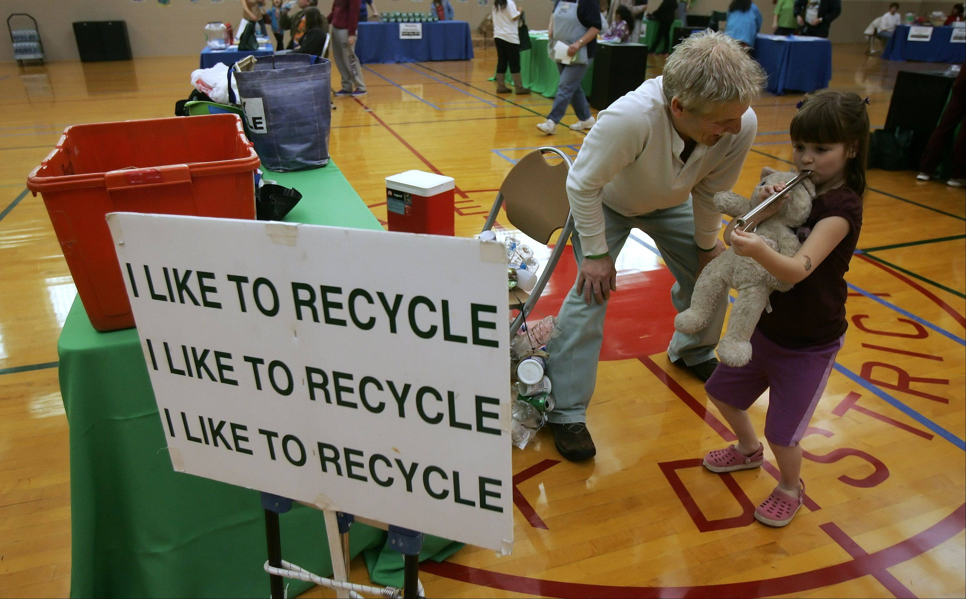 Ricky Recycle (Tom Pilurs) watches as Kathryn Murbach, 6, of Mount Prospect, plays a slide whistle during the Earth Day celebration Sunday at the Wheeling Park District. The event included kite making, seed planting, and story time activities.