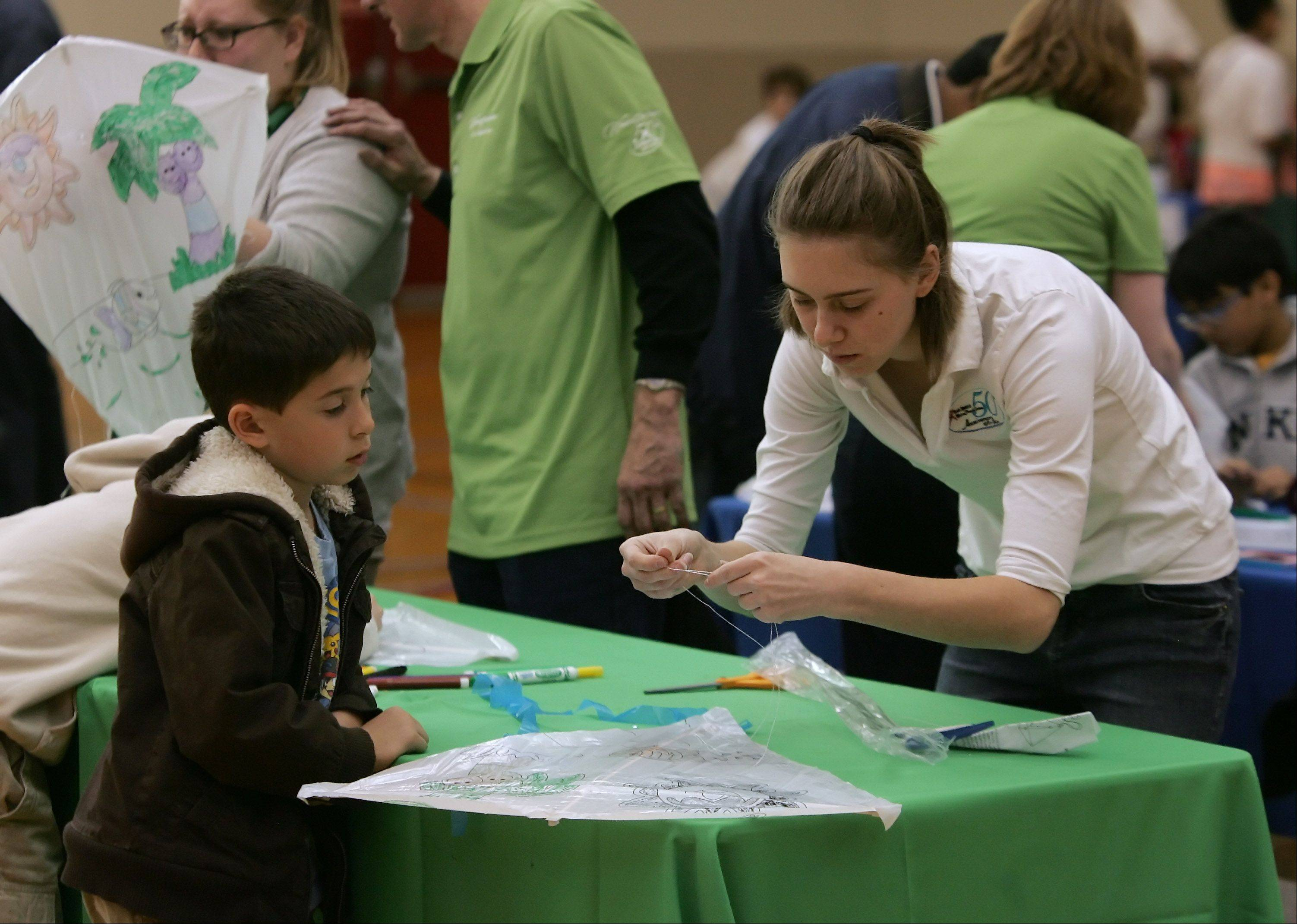Wheeling Park District Fitness Supervisor Sara Kulka helps Adam Shane, 8, of Wheeling, with his kite during the park district's Earth Day celebration Sunday at the Community Recreation Center.