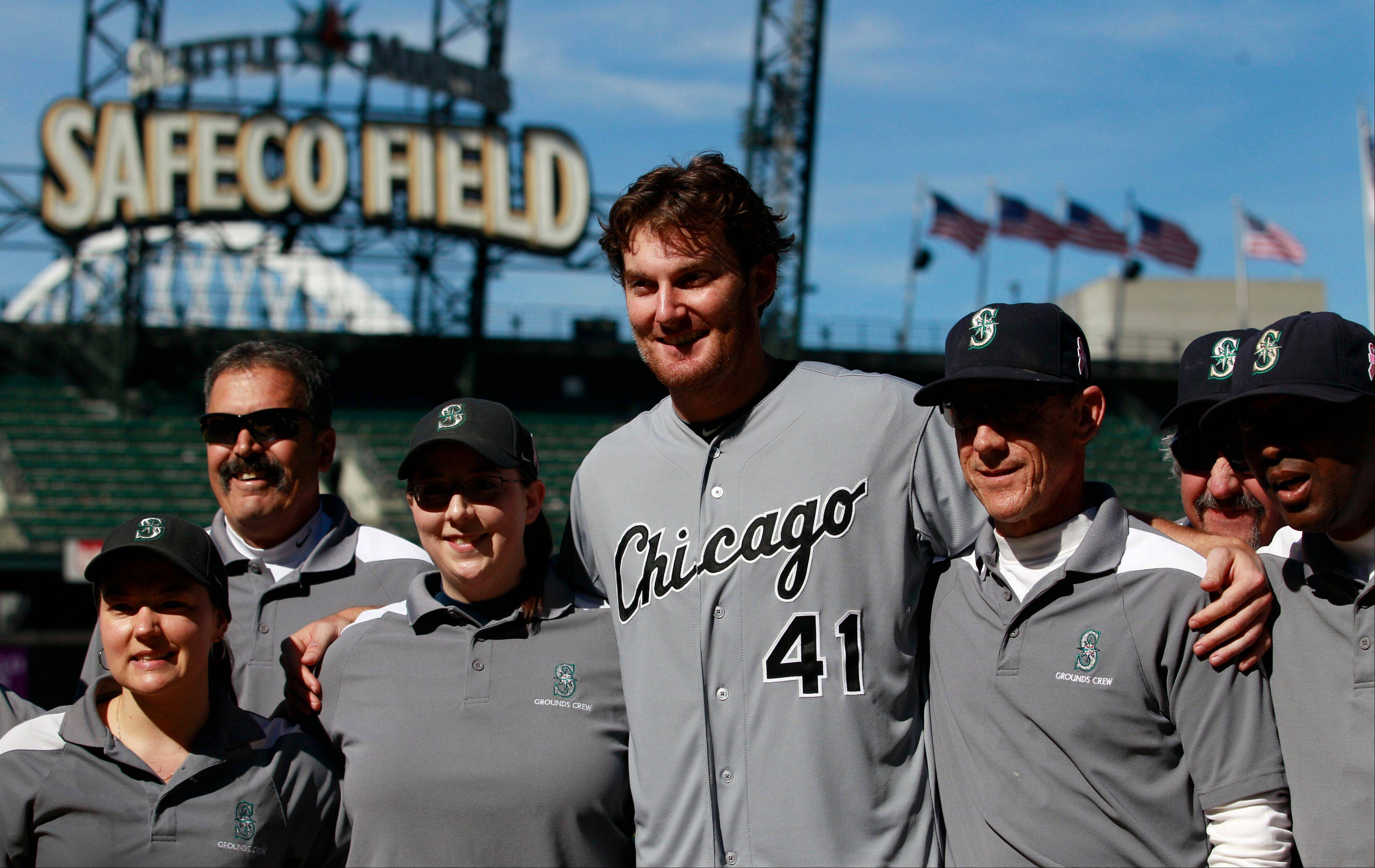 White Sox starting pitcher Phil Humber, center, poses with members of the grounds crew on the pitcher's mound Saturday after pitching a perfect game against the Seattle Mariners in Seattle. The White Sox won 4-0.