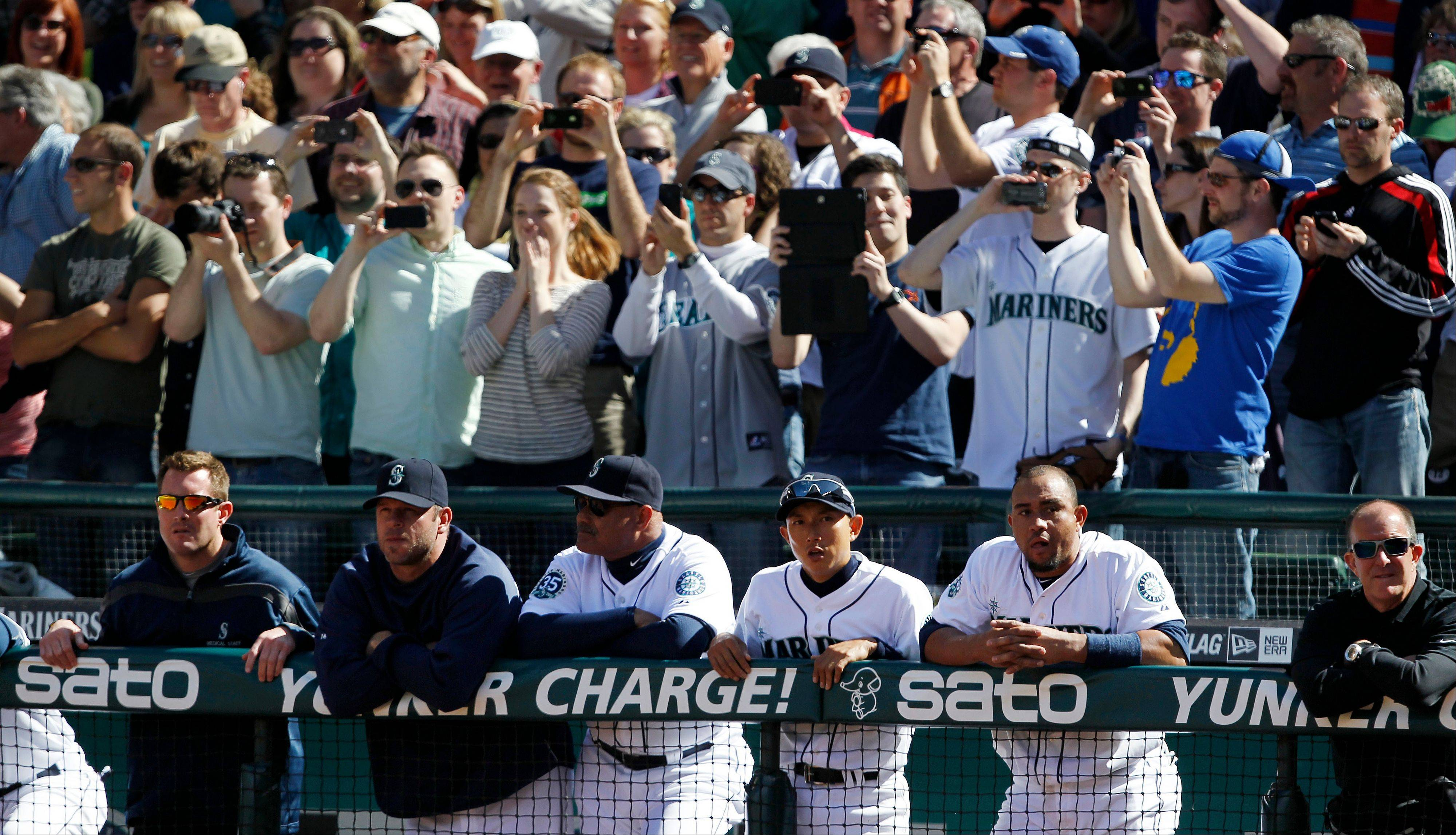 Seattle Mariners players and coaches line the dugout rail as fans, top, stand behind to watch White Sox starting pitcher Phil Humber deliver in the ninth inning.
