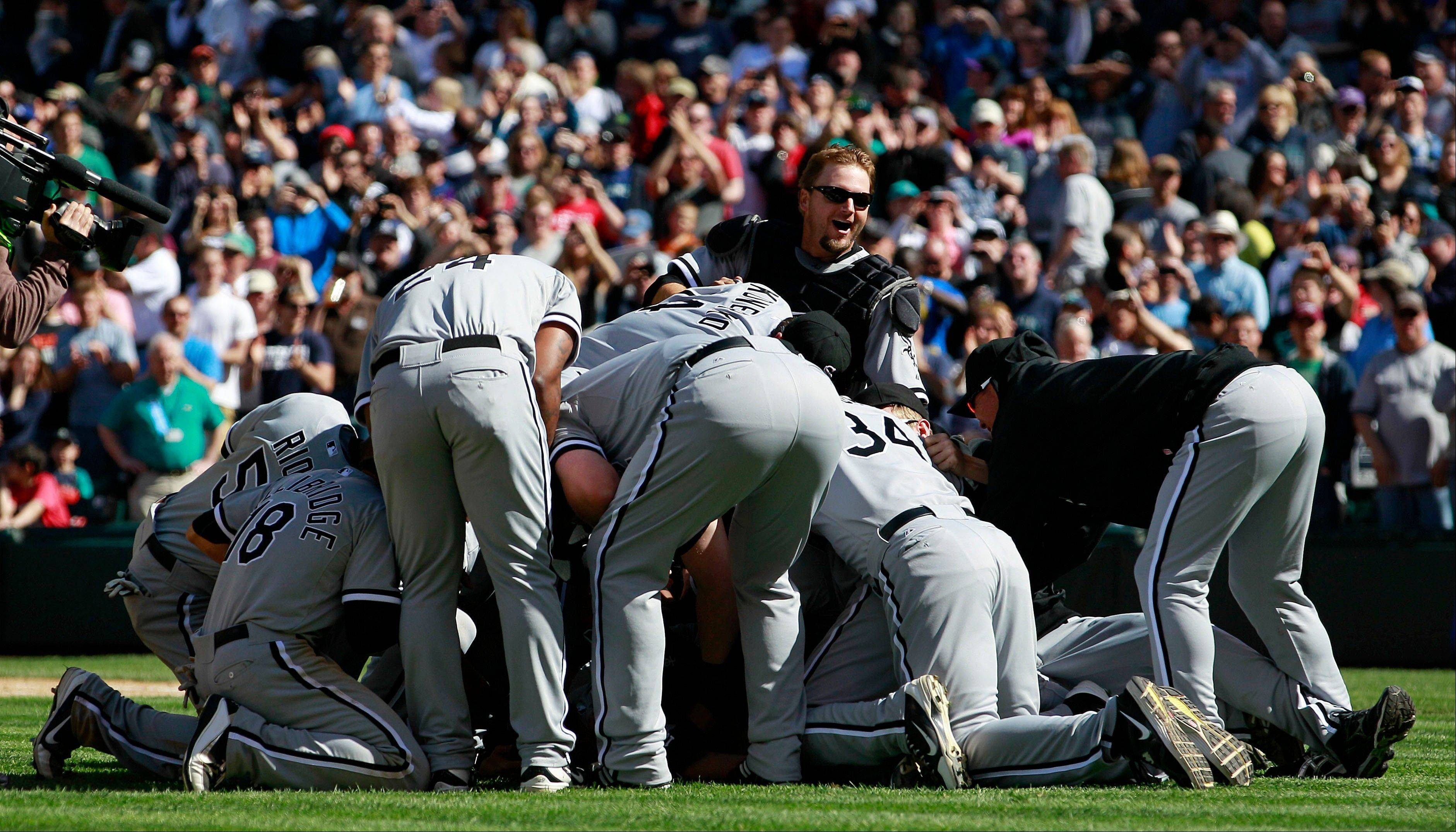 White Sox starting pitcher Phil Humber is mobbed Saturday after pitching a perfect game.