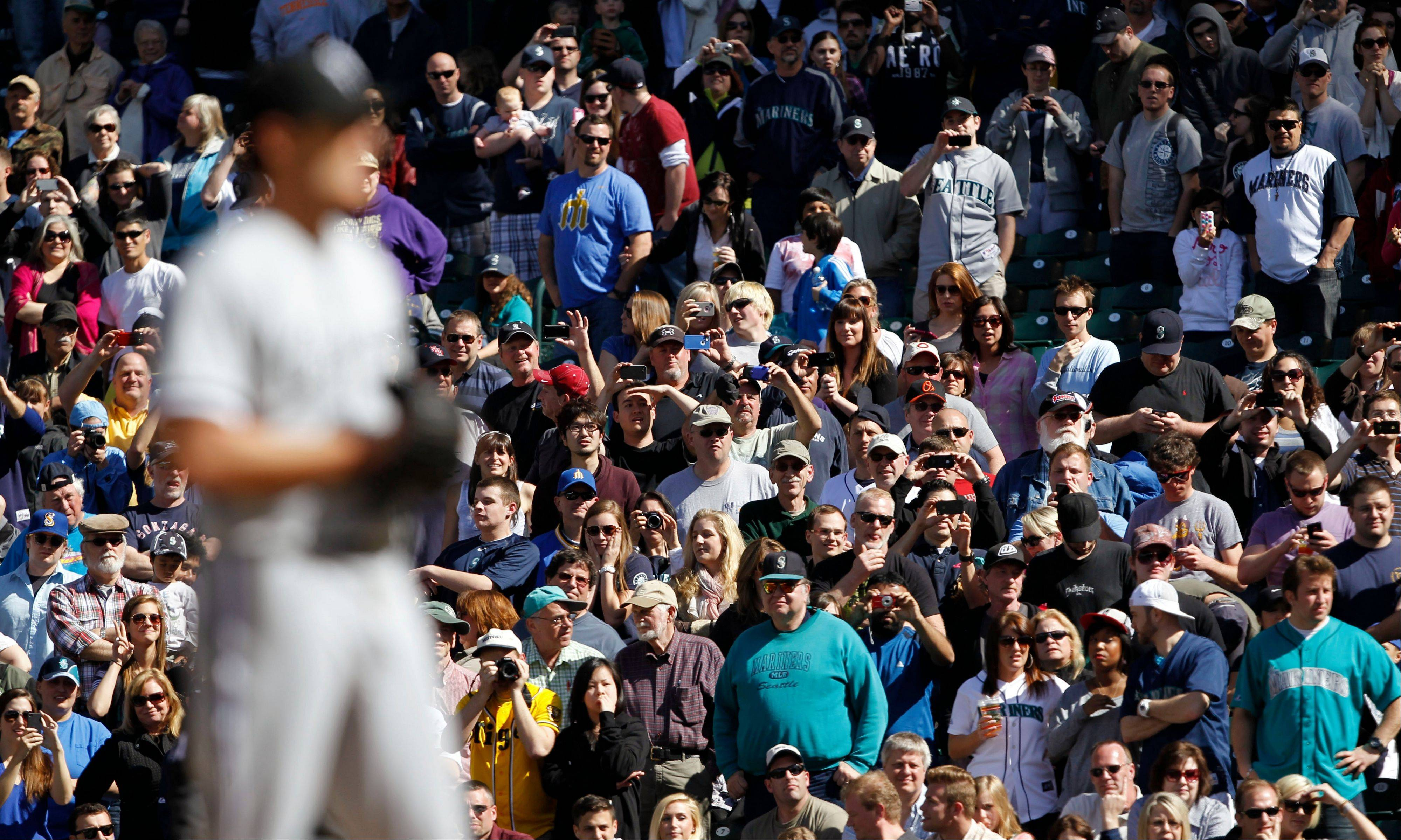 Fans stand as White Sox starting pitcher Phil Humber, foreground, readies to throw with two outs in the ninth inning.