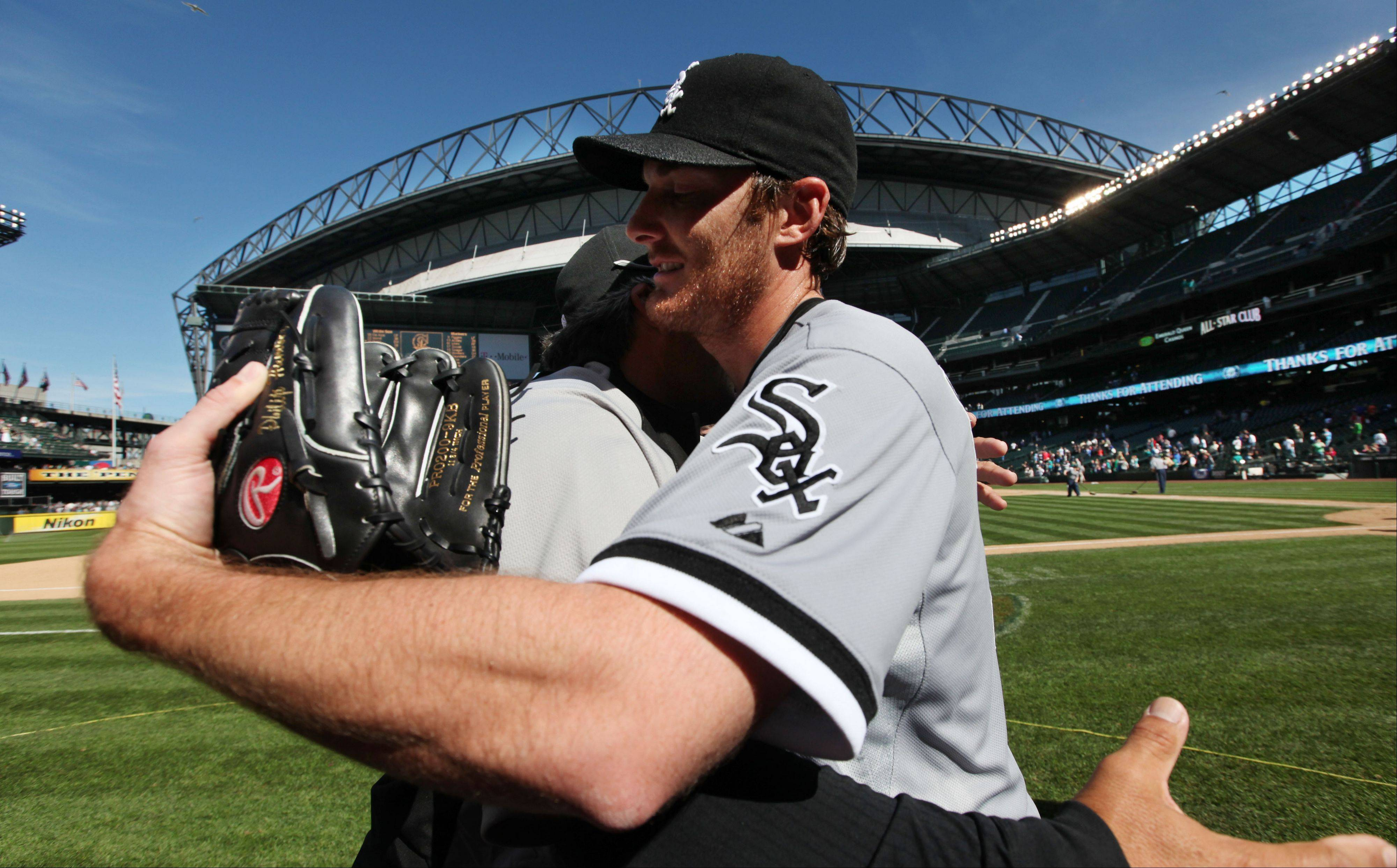 White Sox starting pitcher Phil Humber, right, is hugged Saturday after pitching a perfect game.