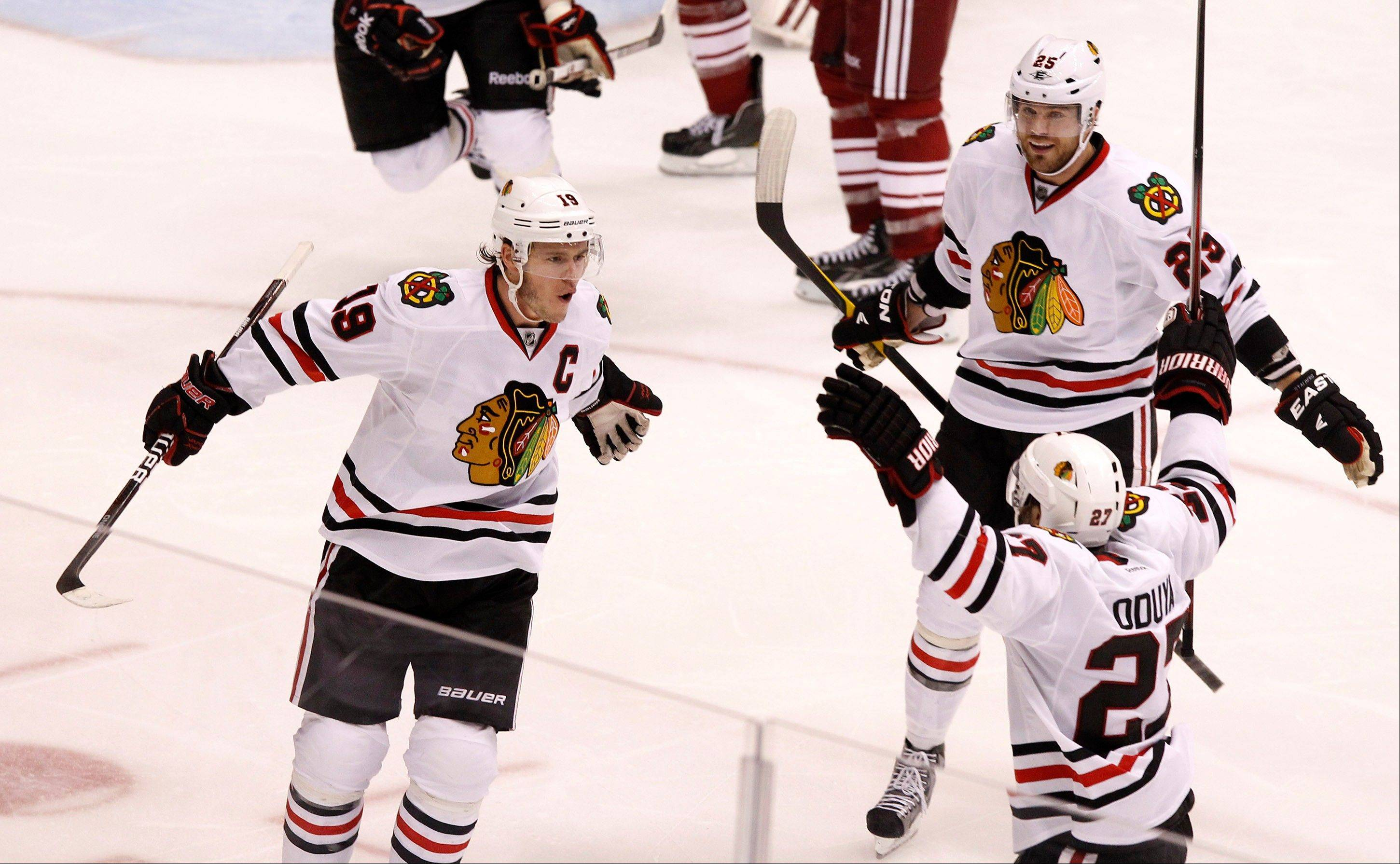 Chicago Blackhawks' Jonathan Toews (19) celebrates his game-winning goal against the Phoenix Coyotes with teammates Viktor Stalberg (25) and Johnny Oduya (27) during overtime in Game 5. The Blackhawks defeated the Coyotes 2-1.