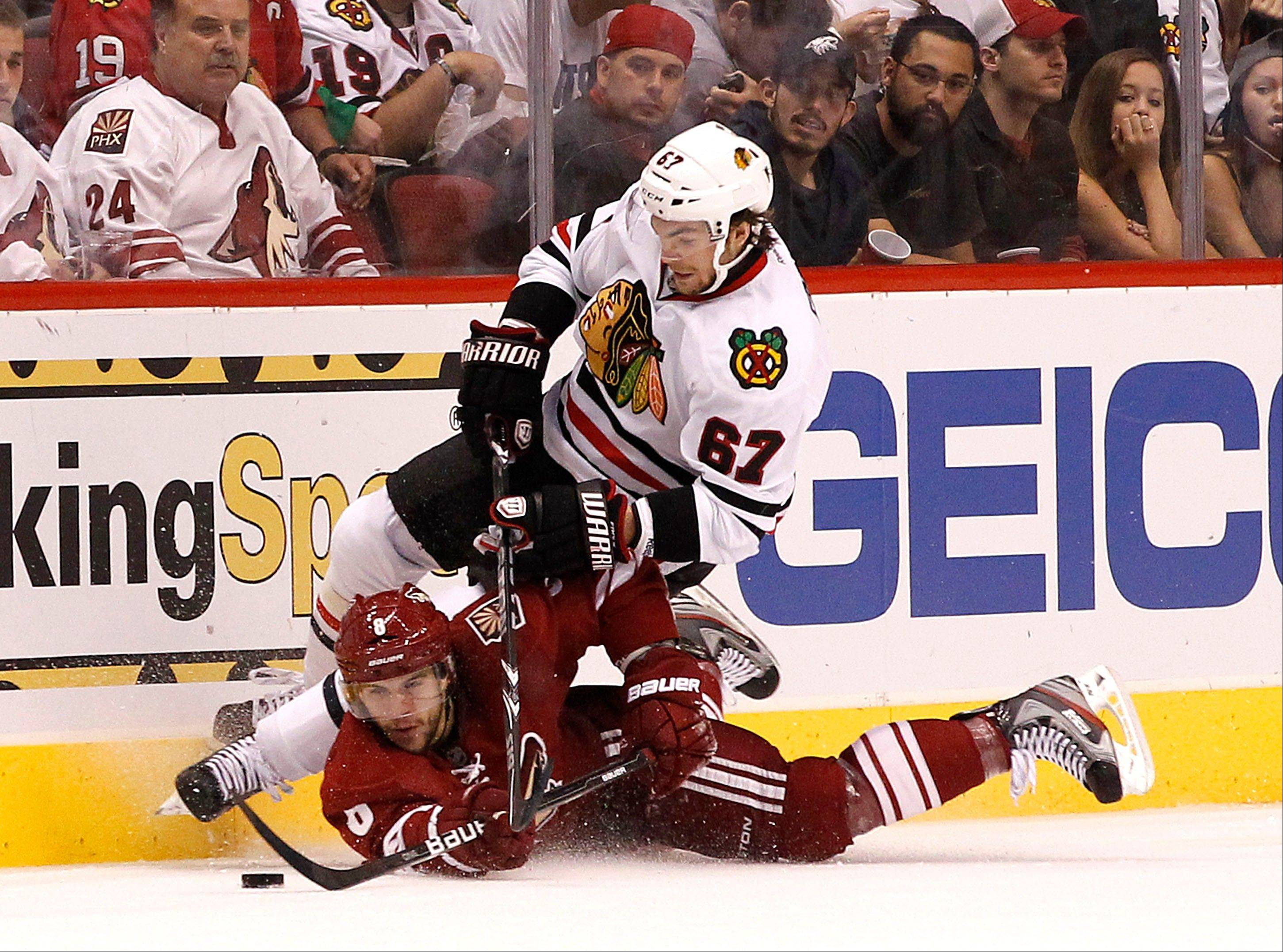 Phoenix Coyotes' Gilbert Brule (8) tries to get control of the puck as Chicago Blackhawks' Michael Frolik (67), of the Czech Republic, falls over him during the second period in Game 5 of an NHL hockey Stanley Cup first-round playoff series Saturday, April 21, 2012, in Glendale, Ariz.