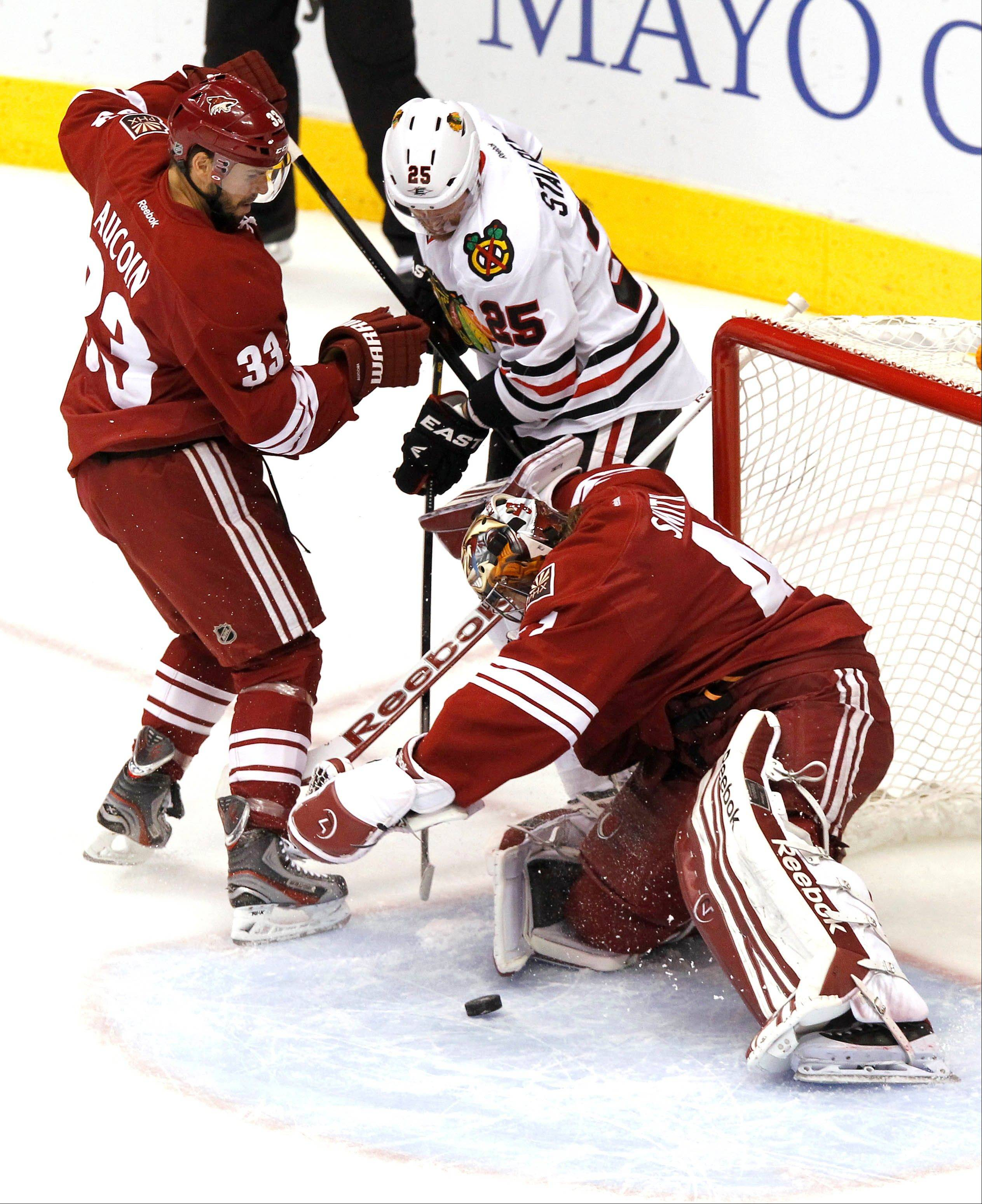 Phoenix Coyotes' Mike Smith, right, makes a save on a shot by Chicago Blackhawks' Viktor Stalberg (25), of Sweden, as Coyotes' Adrian Aucoin (33) defends during the first period in Game 5 of an NHL hockey Stanley Cup first-round playoff series Saturday, April 21, 2012, in Glendale, Ariz.