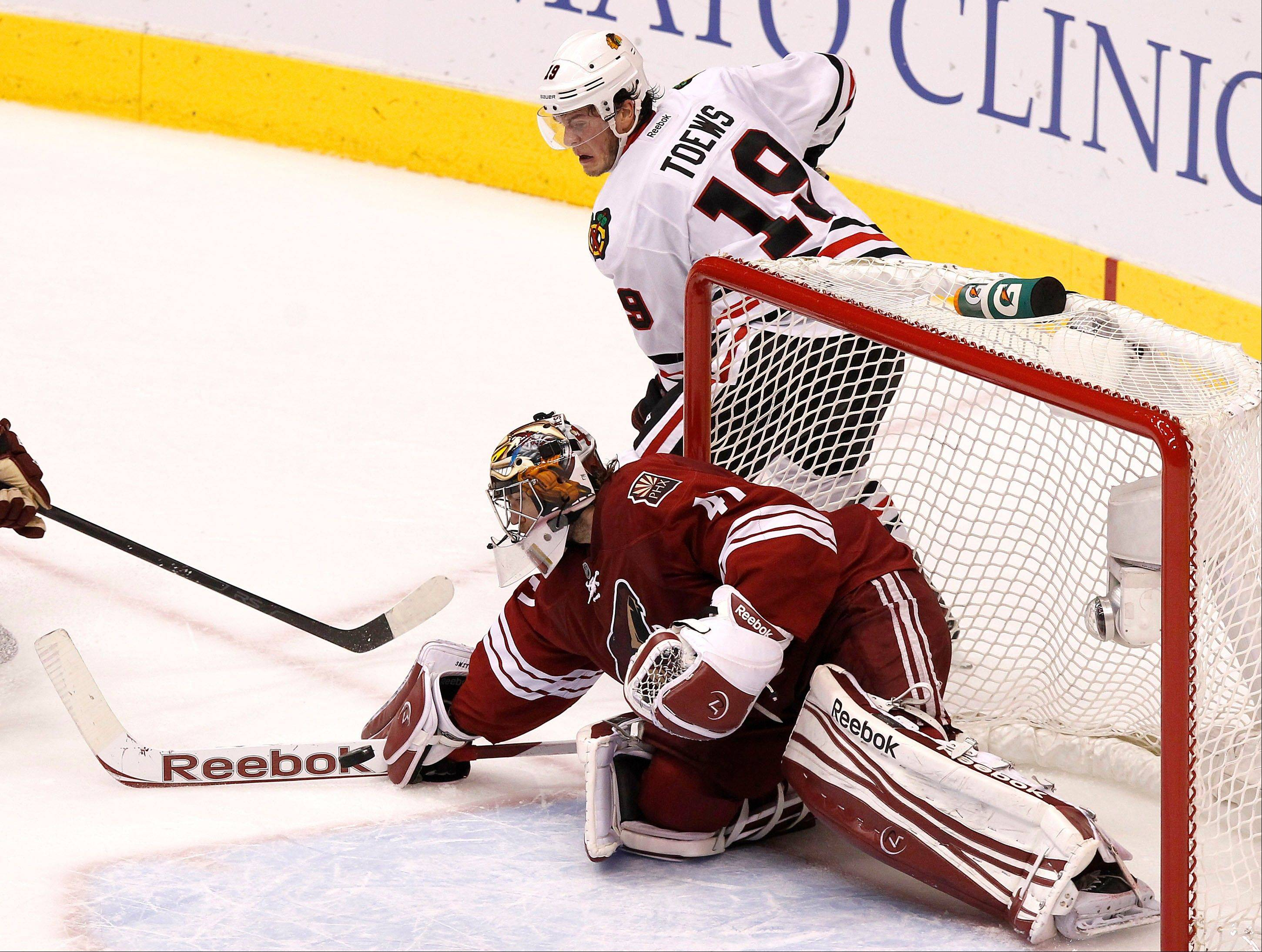 Phoenix Coyotes' Mike Smith, bottom, makes a save on a shot by Chicago Blackhawks' Jonathan Toews (19) during the first period in Game 5 of an NHL hockey Stanley Cup first-round playoff series Saturday, April 21, 2012, in Glendale, Ariz.