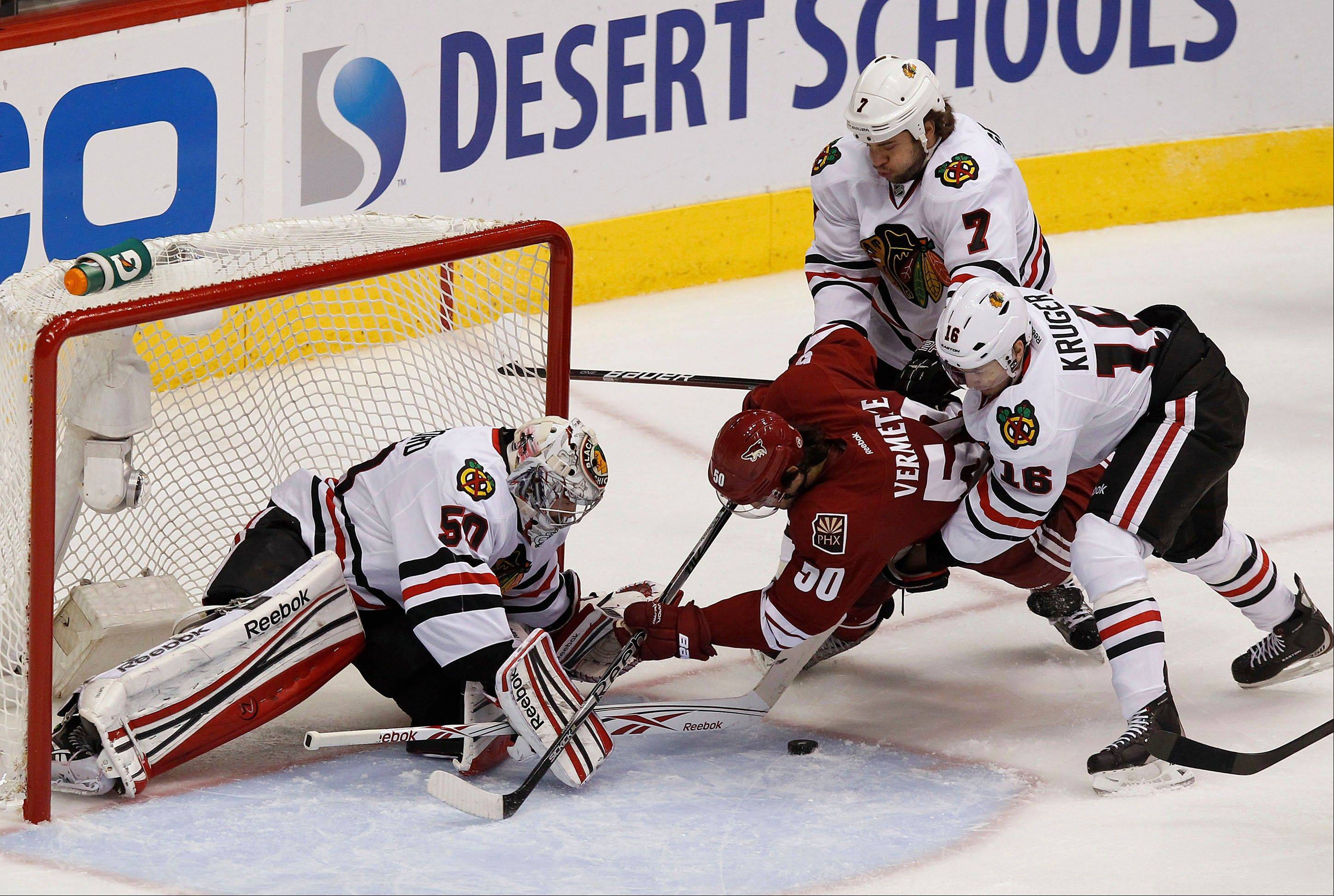 Chicago Blackhawks' Corey Crawford, left, makes a save on a shot by Phoenix Coyotes' Antoine Vermette (50) as Blackhawks' Marcus Kruger (16), of Sweden, and Brent Seabrook (7) defend during the first period in Game 5 of an NHL hockey Stanley Cup first-round playoff series Saturday, April 21, 2012, in Glendale, Ariz.