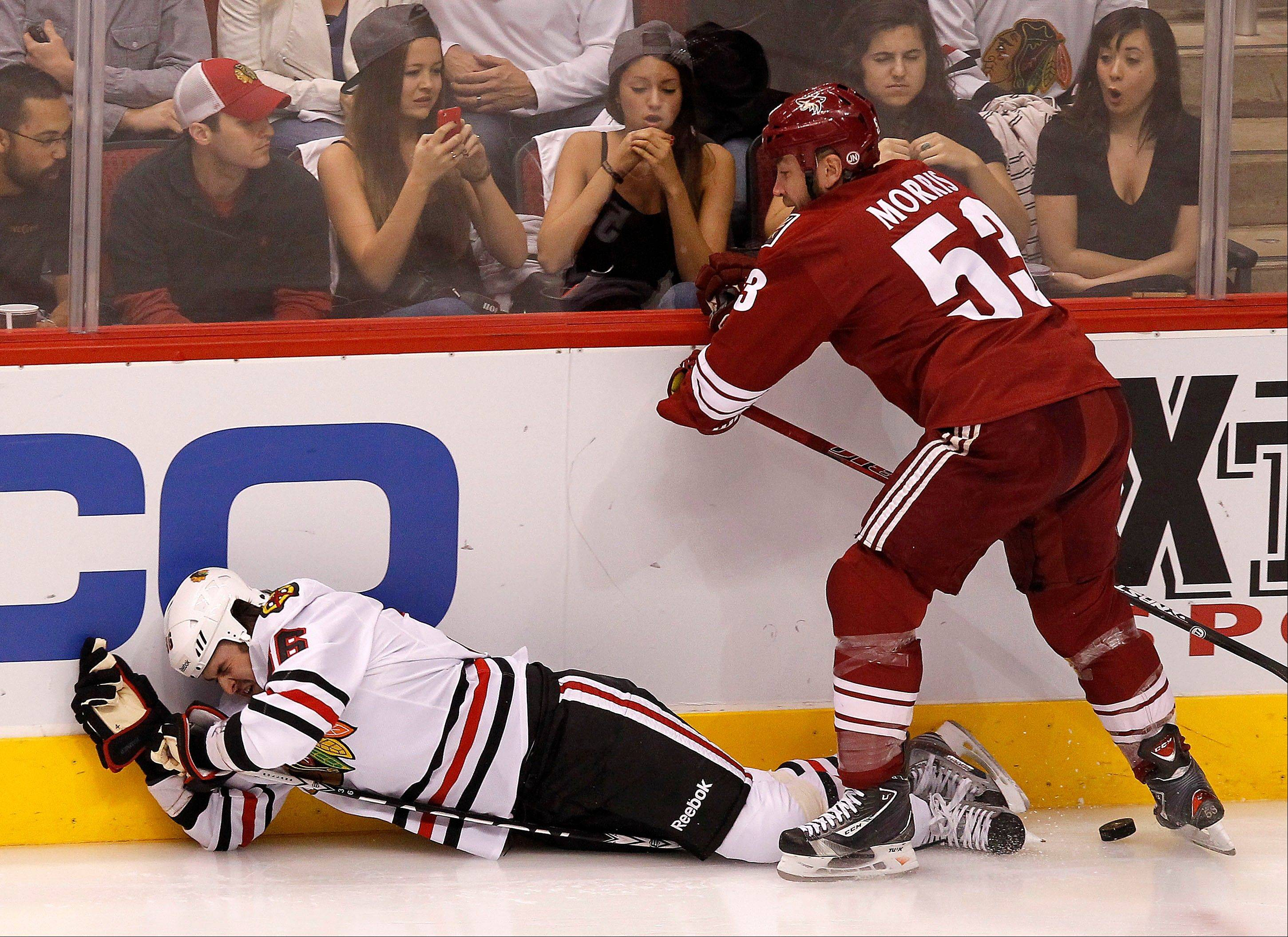 Phoenix Coyotes' Derek Morris, right, checks Chicago Blackhawks' Dave Bolland to the ice during the first period in Game 5 of an NHL hockey Stanley Cup first-round playoff series Saturday, April 21, 2012, in Glendale, Ariz.