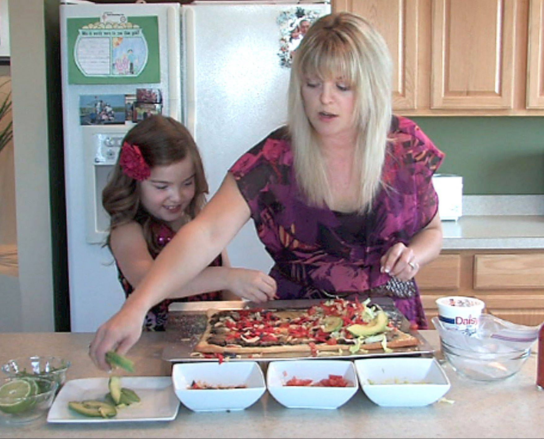 Jennifer Loiseau and her 7-year-old daughter, Maria, add lettuce, tomato, chips and guacamole to taco pizza in thier Lake in the Hills kitchen. She produces an online video cooking blog called AmateurKitchen.tv.