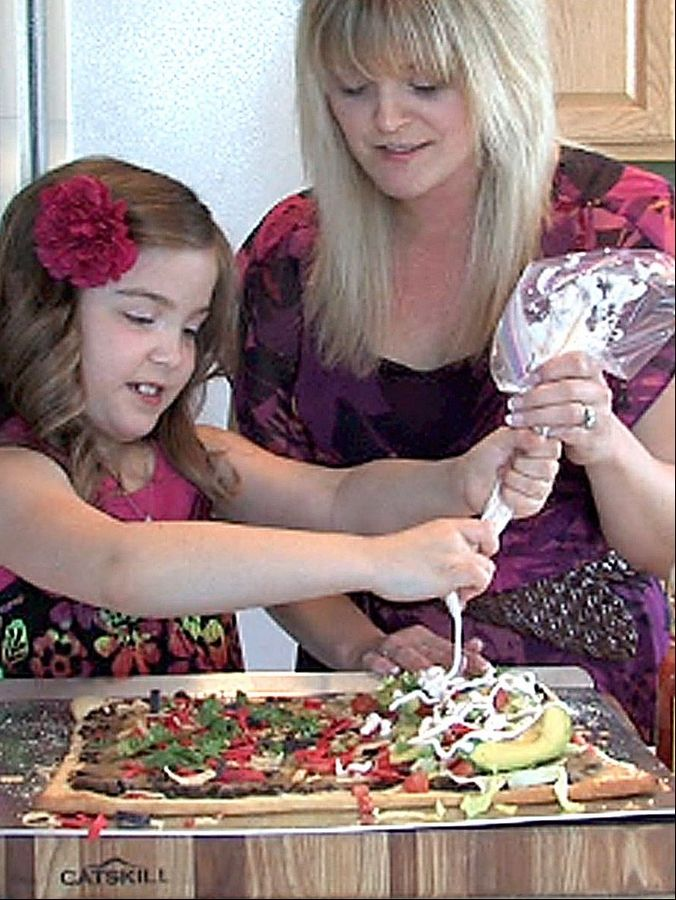 Cook of the Week Jennifer Loiseau and her 7-year-old daughter Maria use a sour cream mix as piping on their taco pizza in their Lake in the Hills kitchen. She produces an online video cooking blog called AmateurKitchen.tv