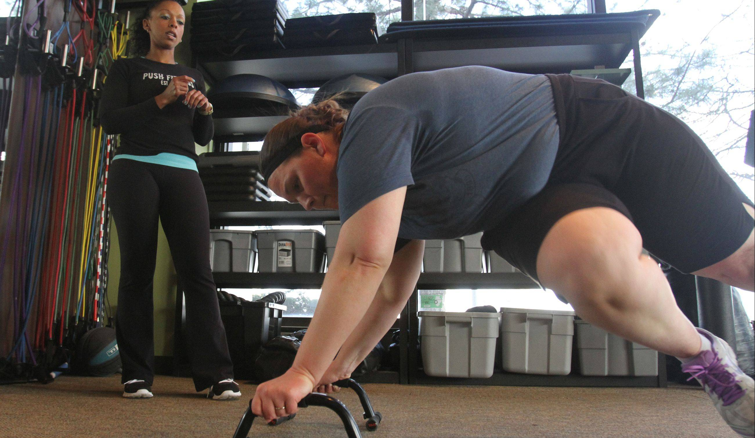 Trainer Michelle Amsden looks on as Katie Przyszlak works out her hips.
