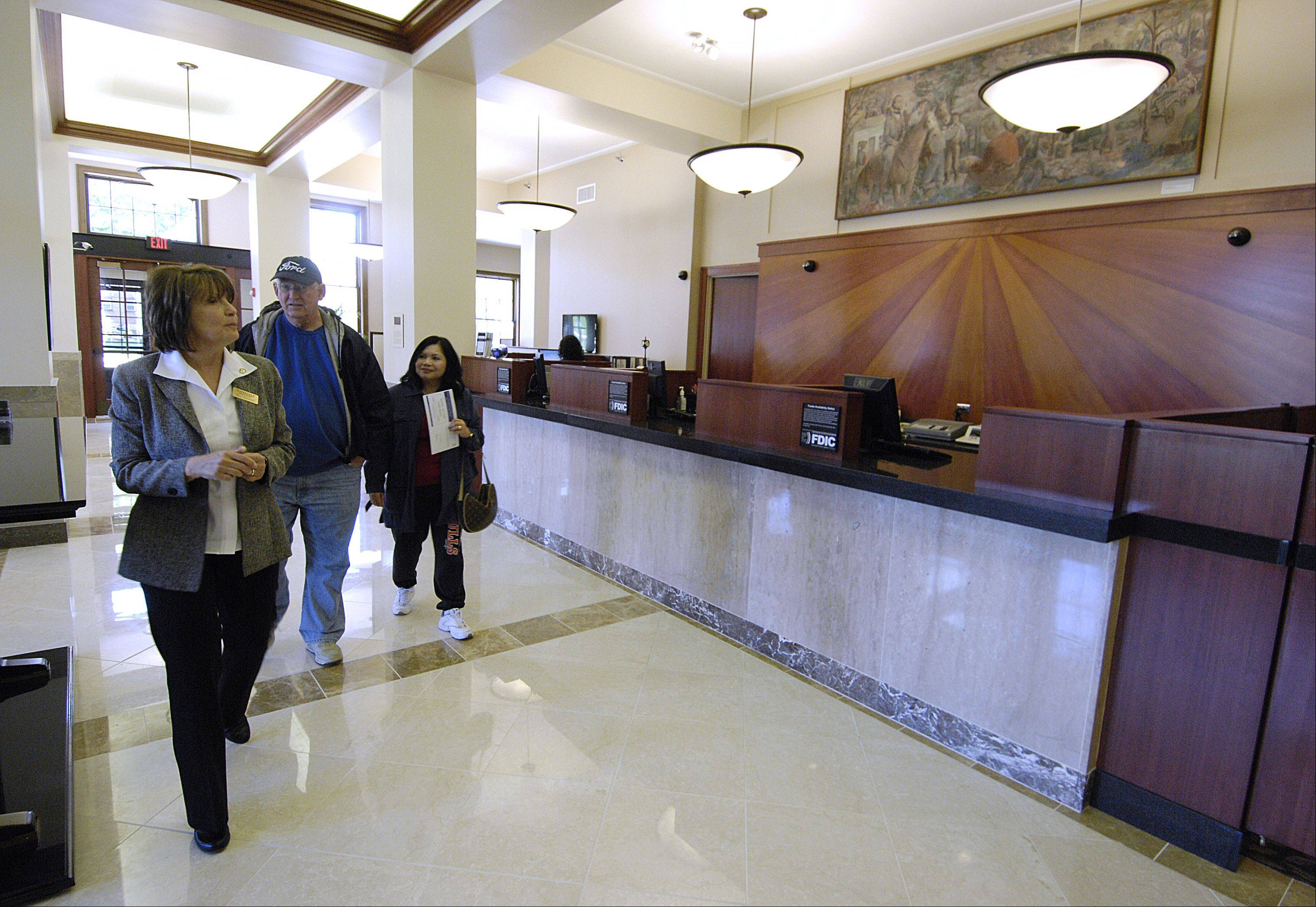 Senior personal banker Terri Spizzirri gives Steve and Tess Dinnsen of Naperville a tour of the new Naperville Bank & Trust on Washington Street. The bank opened for business Monday morning.