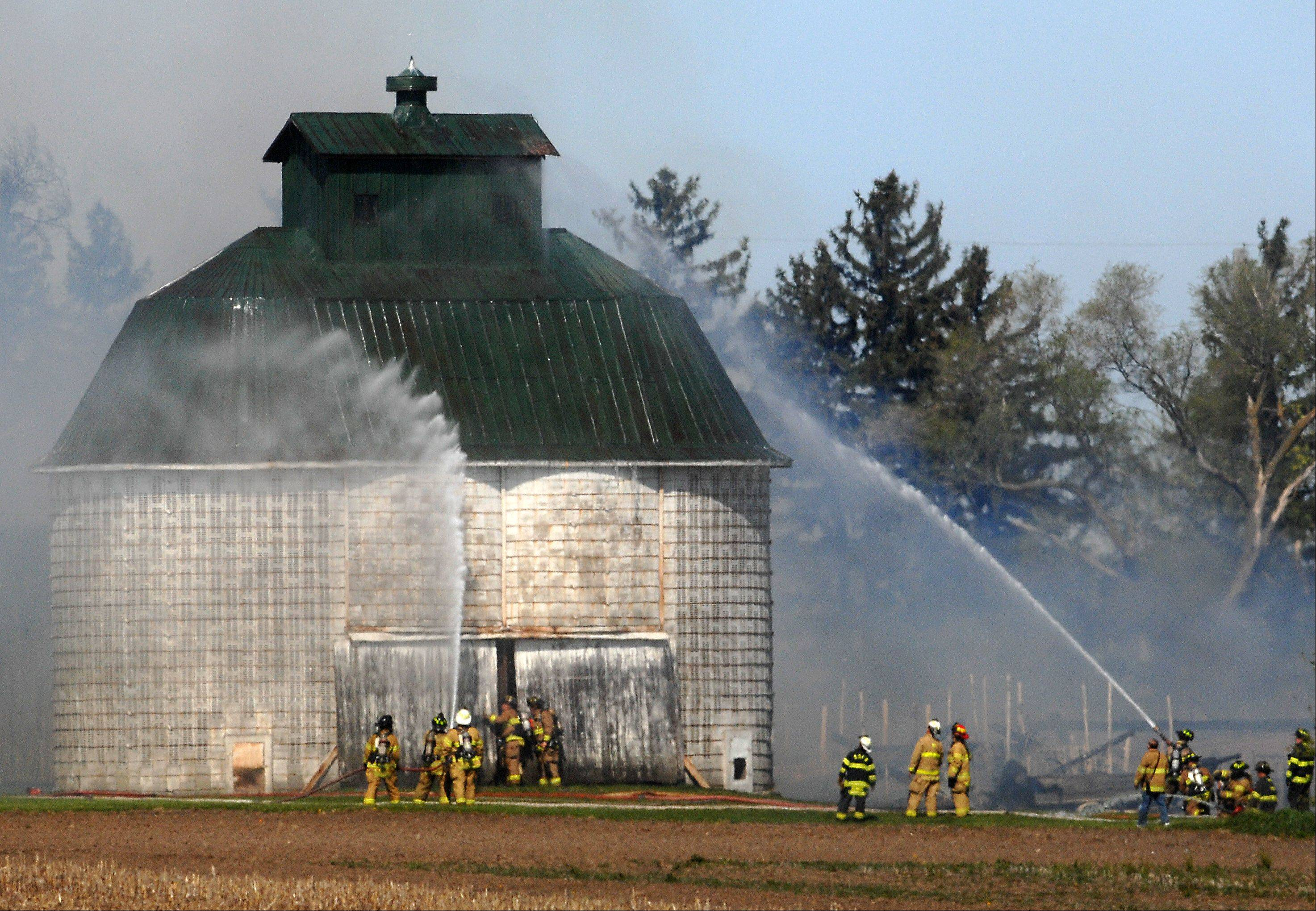 Firefighters hose down a building to try and save it from catching fire Monday morning near Lily Lake.