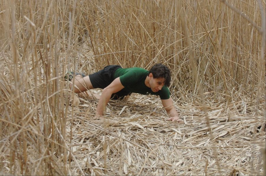 Anthony Matesi of Carol Stream trains for the Spartan Death Race in June by practicing his crawl at Mallard Lake Forest Preserve near Hanover Park.