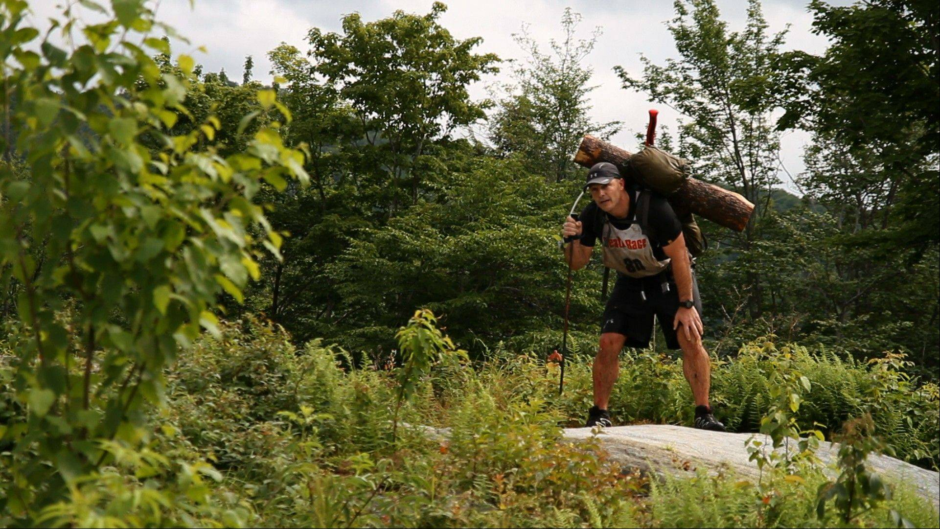 The 2011 winner, Joe Decker, hoists a log as he traverses the Death Race course last year.