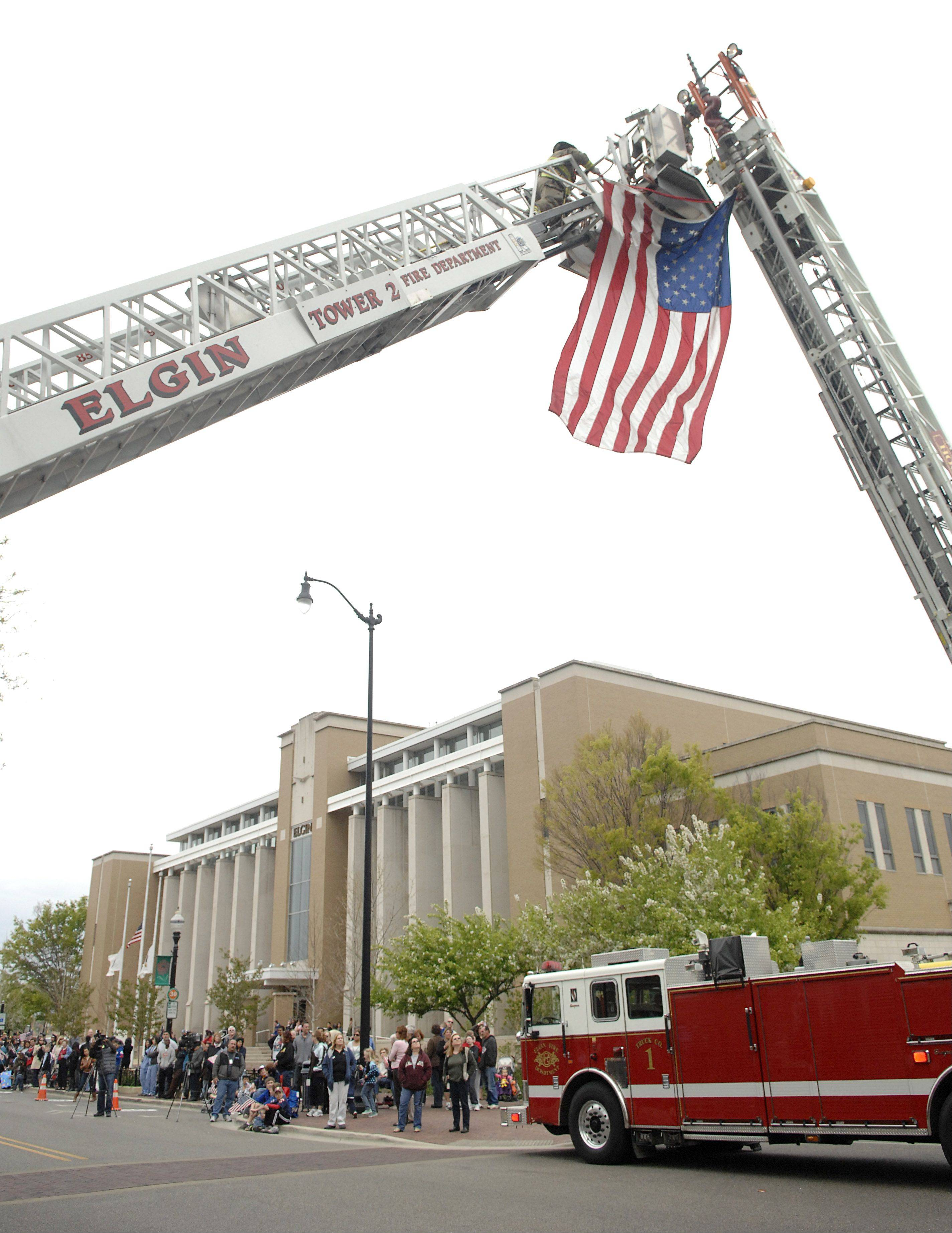 Elgin firefighters unfurl the flag for the procession of fallen Marine CPL Alex Martinez to drive under at the intersection of Douglas St. and Dexter Ct. in downtown Elgin on Friday, April 13.