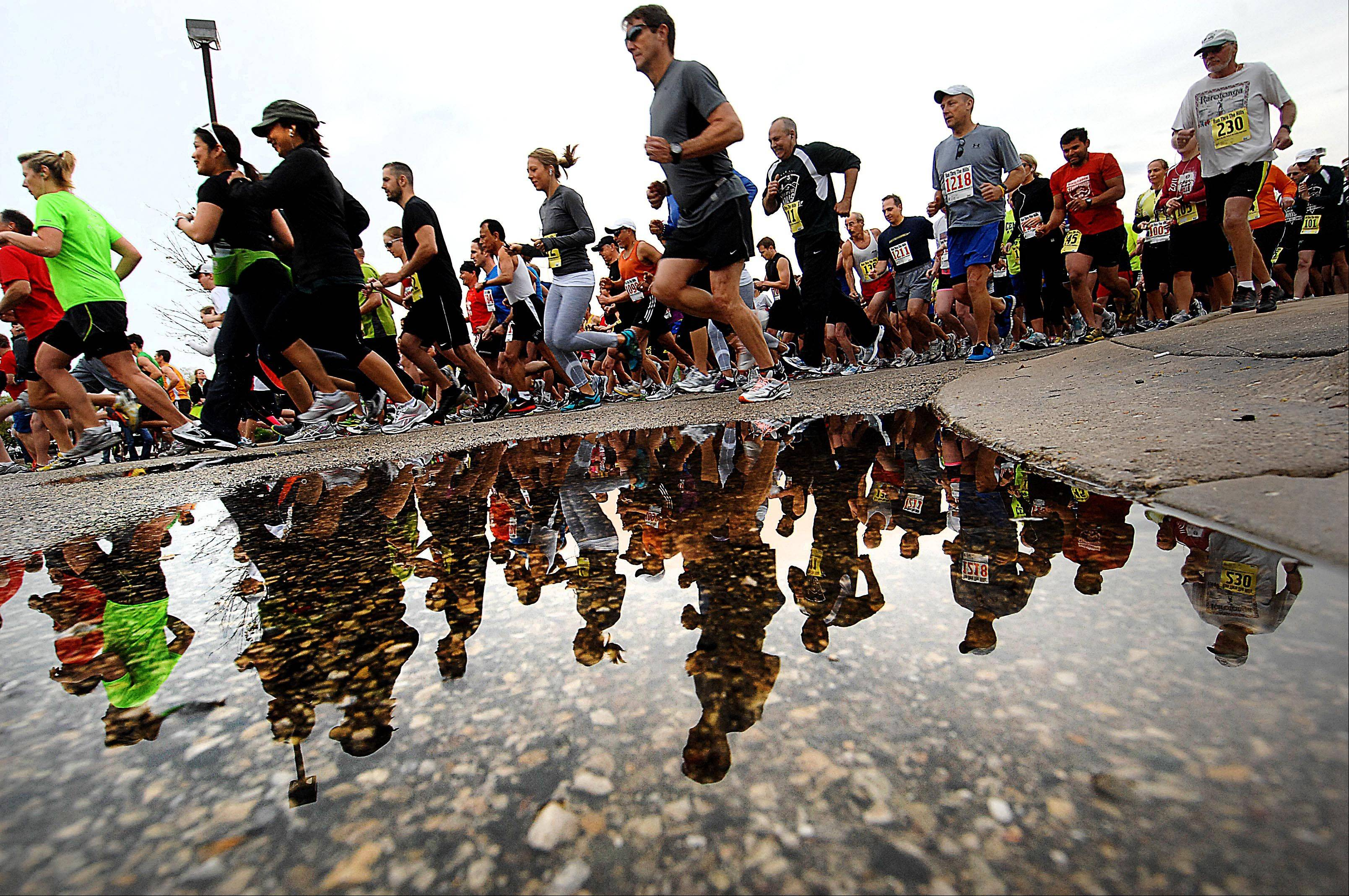 Racers are reflected in a puddle at the start of Sunday morning's Run Through The Hills 5K and 10K road races in Lake in the Hills.