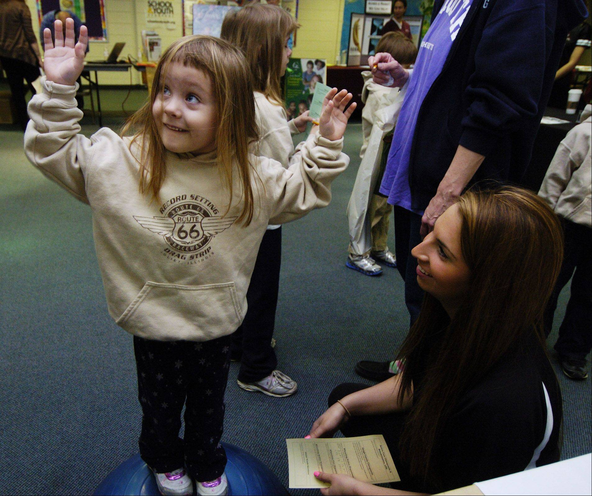 Natalie Edstrom, 5, of Wheeling learns about balance from the Wheeling Park District staff including Jacqueline McCraren during the Wheeling Township and Elementary District 21 wellness fair at Jack London Middle School in Wheeling Saturday.