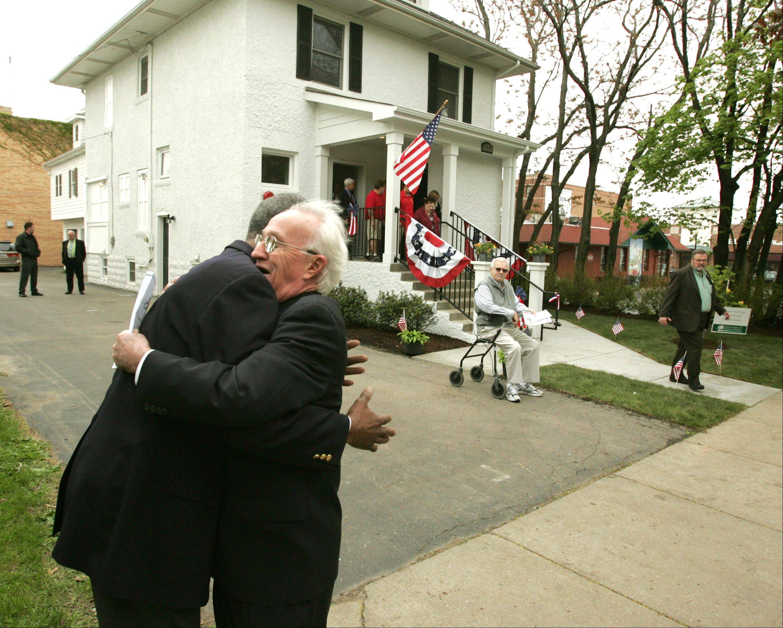 The Midwest Shelter for Homeless Veterans in Wheaton dedicates its new home for veterans in honor of Staff Sgt. Robert J. Miller, who received the Medal of Honor after being Killed in 2008 in Afghanistan. Above, Bob Adams, right, president of the Midwest Shelter Board, greets veteran Gordon Burkhalter following the dedication.
