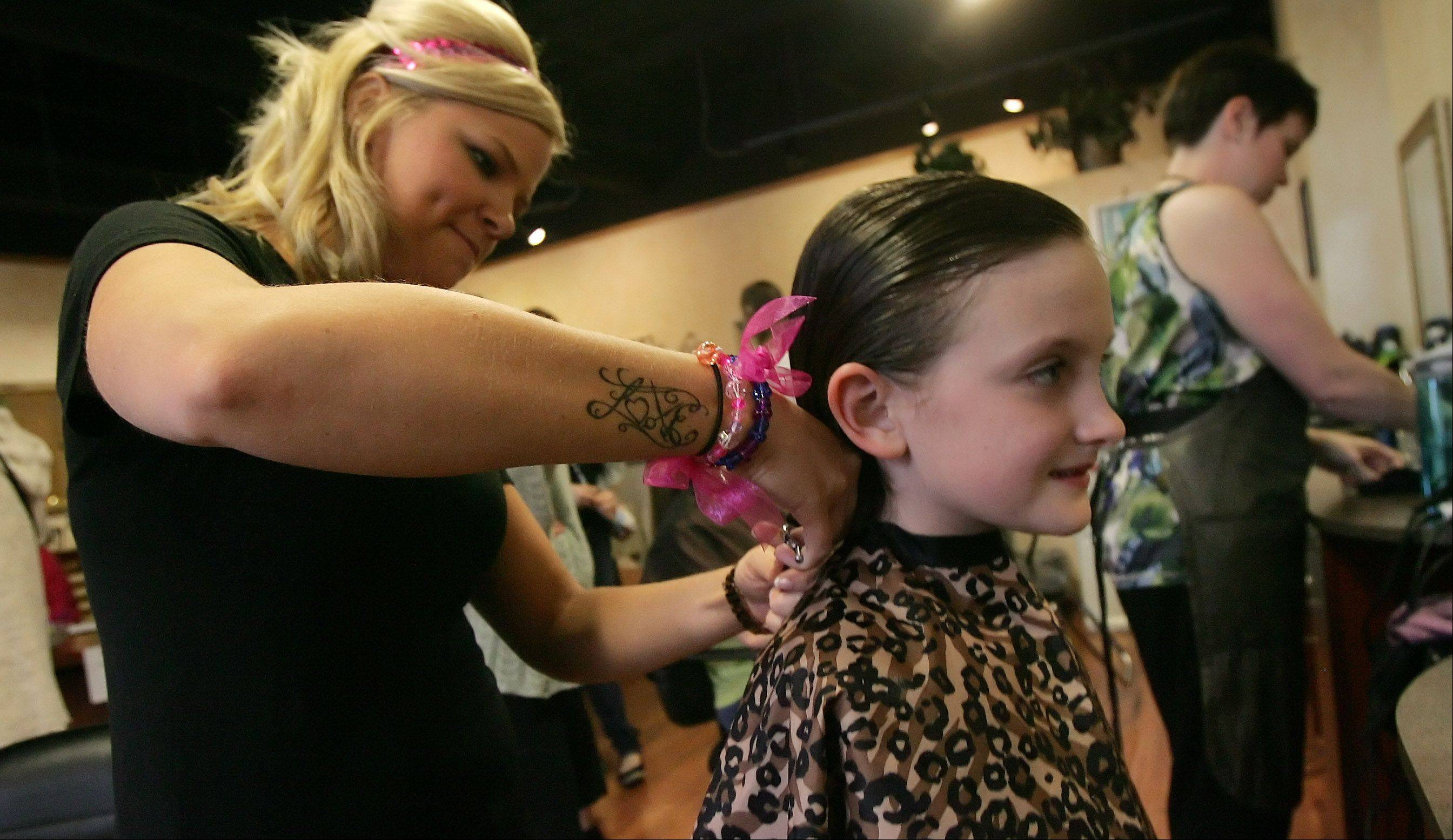 Gilbert R. Boucher II / gboucher@dailyheraldEight-year-old Hannah Connolly, of Mount Prospect, has over 10 inches of her hair cut off by stylist Sara Mock to donate to Locks of Love during Haircuts For Hope Sunday at Halo Hair & Nails in Mount Prospect. The event was to benefit Linda Frahm, who is battling cancer, and was Connolly's teacher at Lions Park School in Mount Prospect.