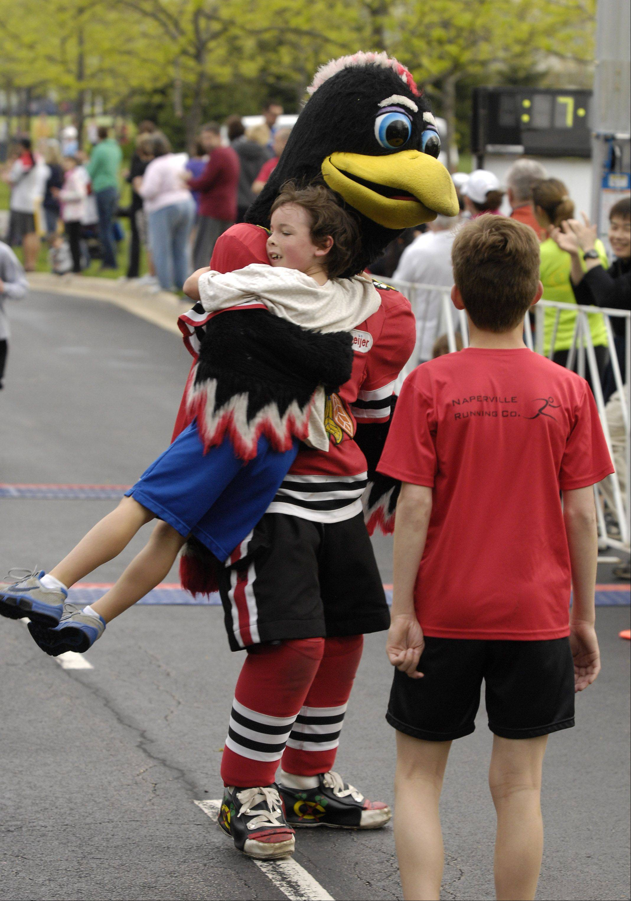 "Liam Cahill, 7 of Naperville places 3rd in the children's race and get spinning hug from Chicago Blackhawks mascot ""Tommy Hawk"" as he crosses the finish line, during the 360 Youth Services� Spring Ahead Run at the Calamos Corporate Campus in Naperville, Sunday."