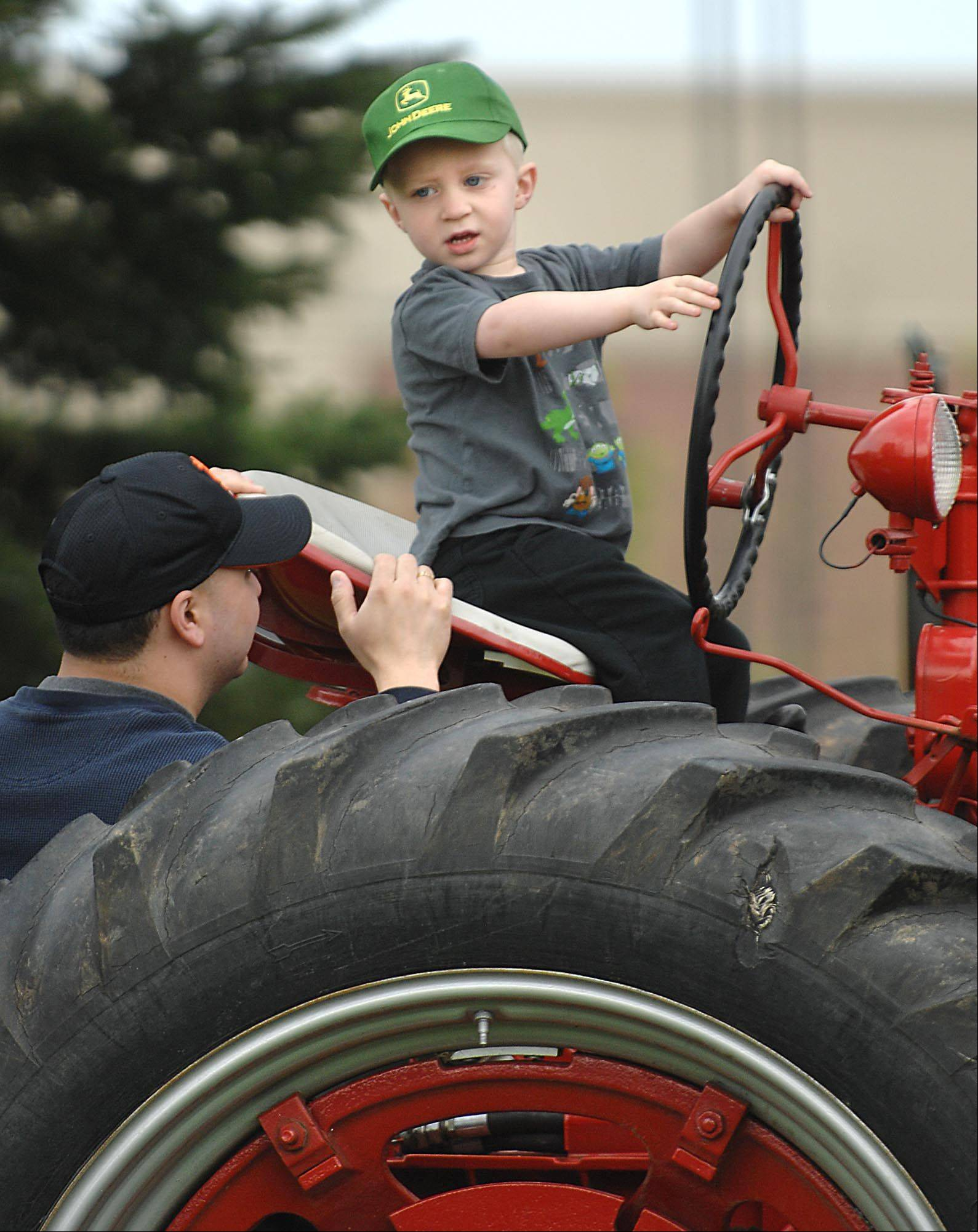 Sebastian Gruener, 3, sits on an antique Farmall tractor Sunday at the Kane County Farm Bureau's annual Touch-A-Tractor event on Randall Road in St. Charles. He was with his mother Coreen of Batavia.