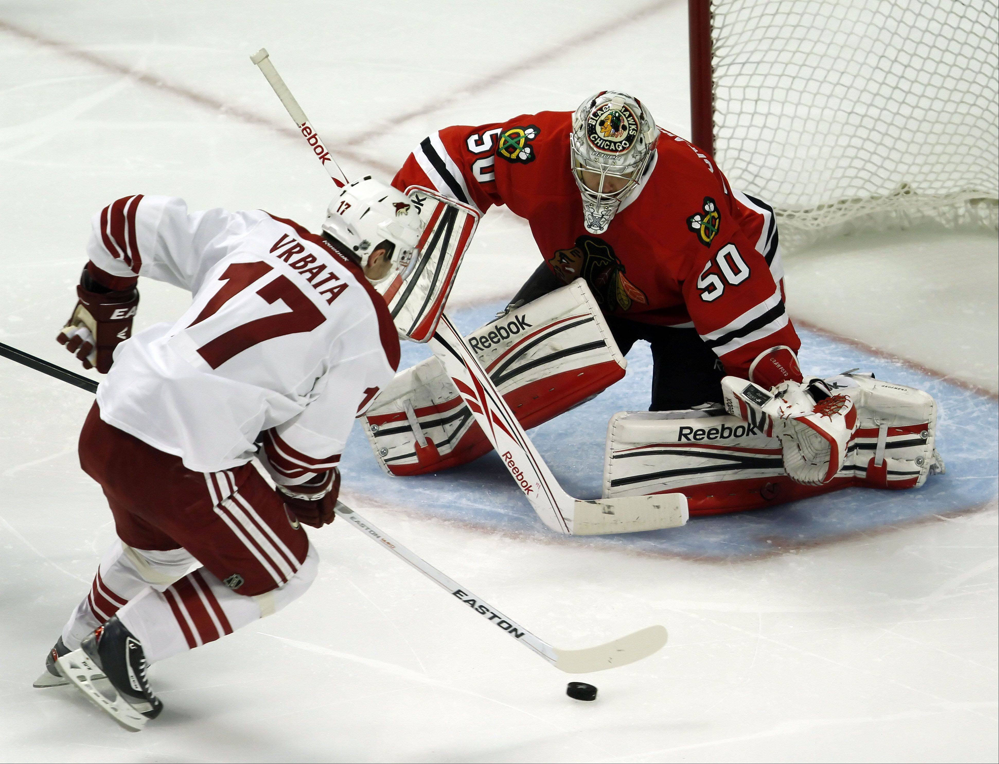 Phoenix Coyotes' right wing Radim Vrbata drives on Chicago Blackhawks' goalie Corey Crawford.