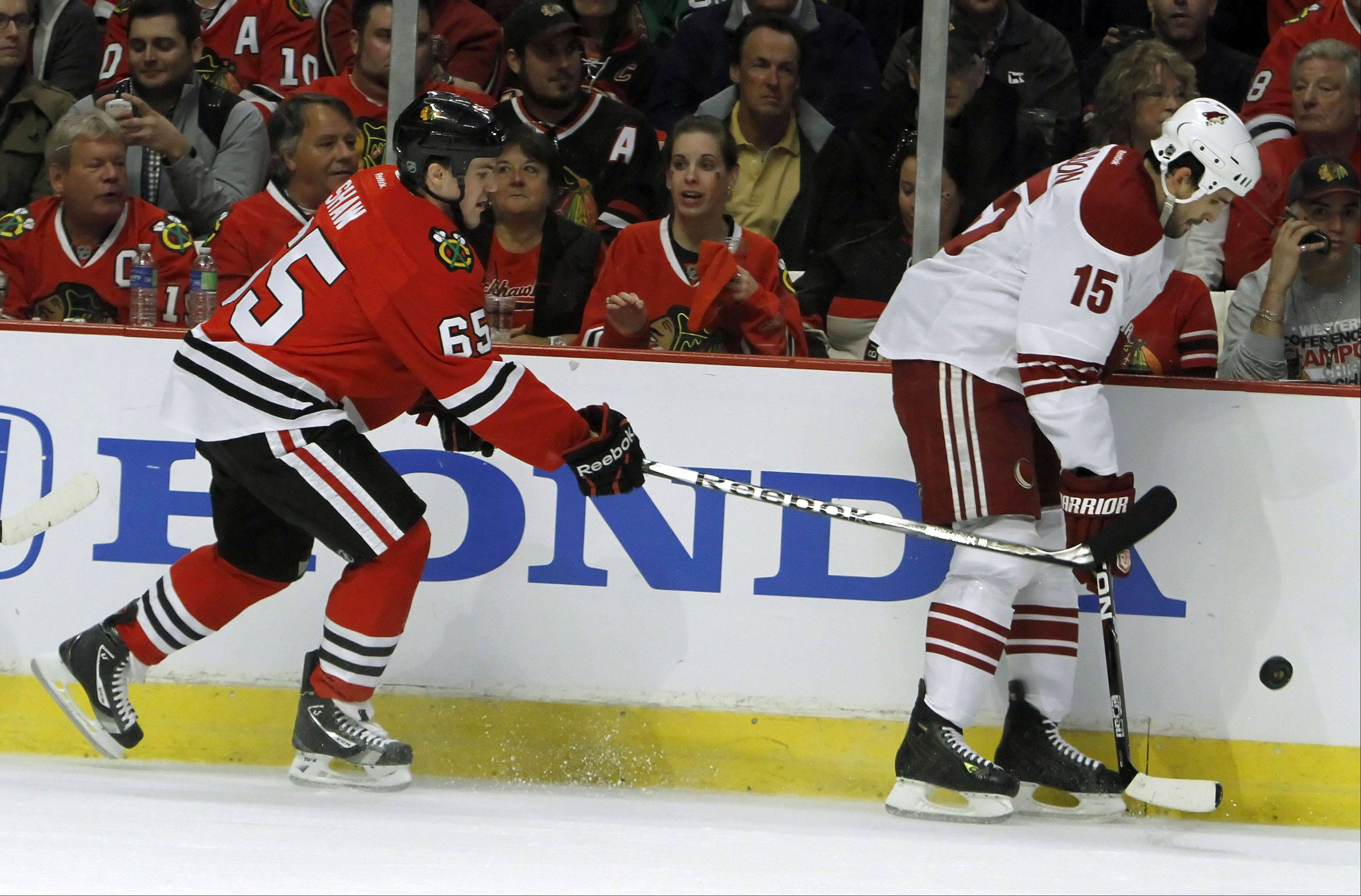 Chicago Blackhawks' center Andrew Shaw battles for the puck with Phoenix Coyotes' center Boyd Gordon .