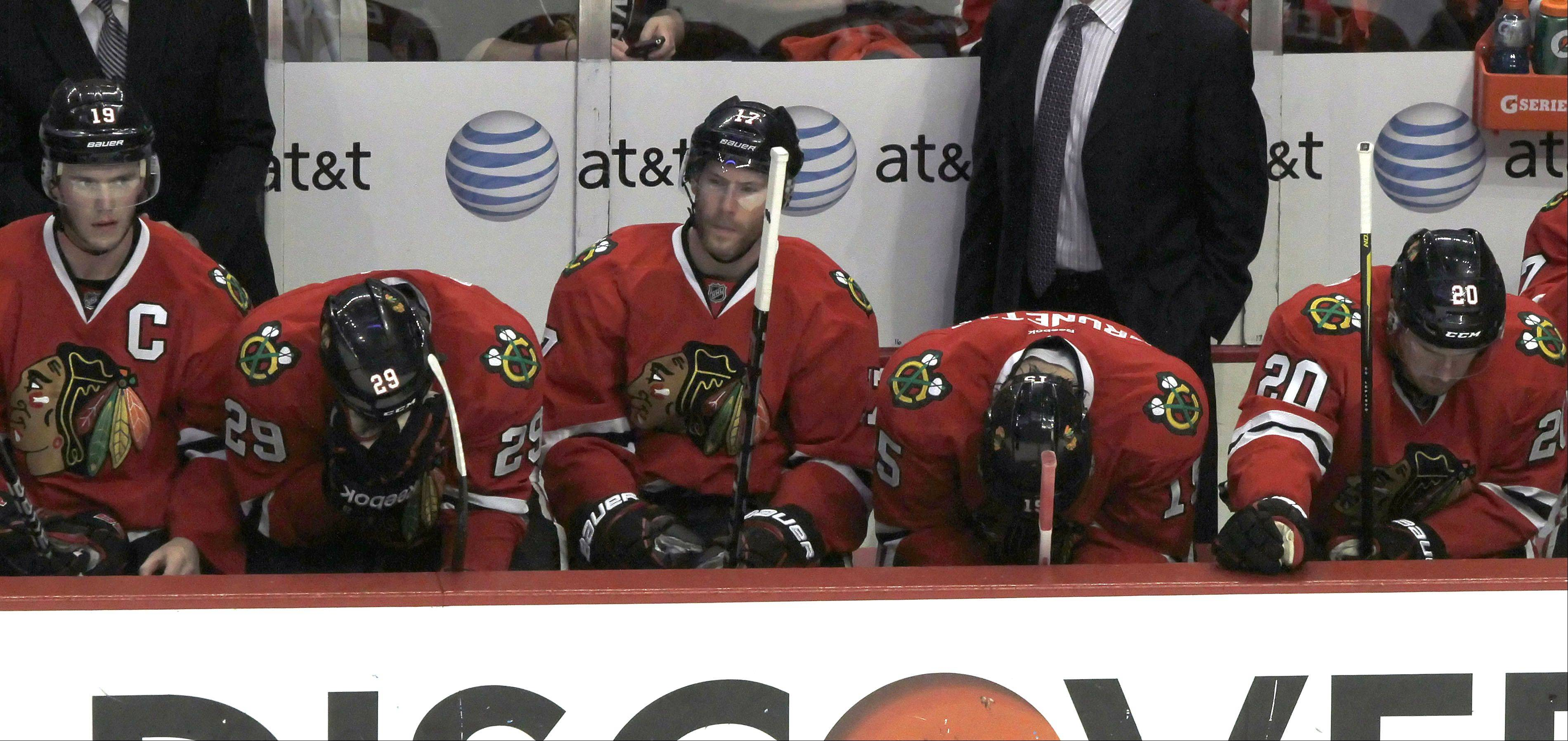 Blackhawks hang their heads on the bench as the game ends.