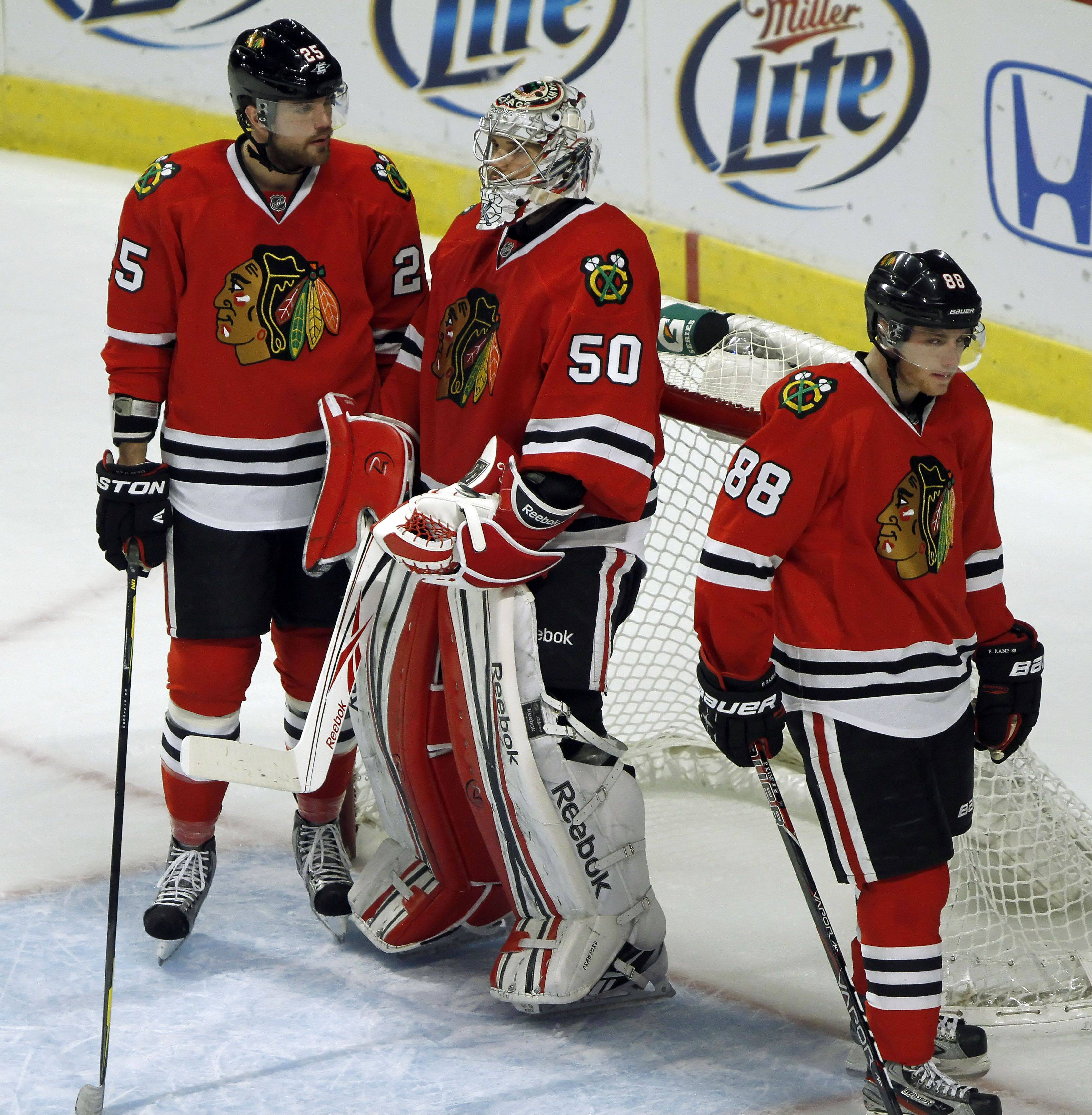 Chicago Blackhawks' left wing Viktor Stalberg and right wing Patrick Kane talk with goalie Corey Crawford after the Coyotes' fourth goal.