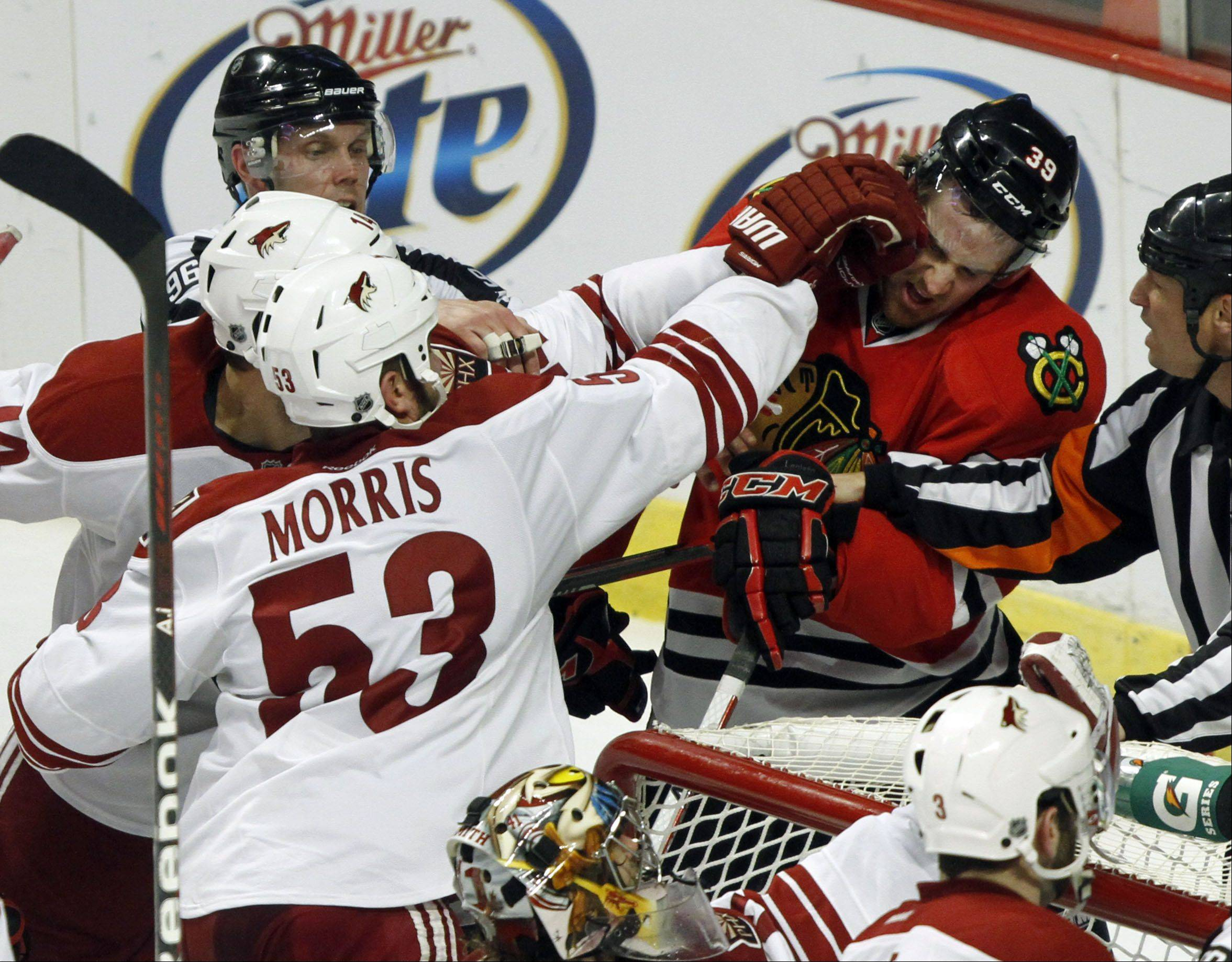 Chicago Blackhawks' right wing Jimmy Hayes and Phoenix Coyotes defenseman Derek Morris get into a tussle.