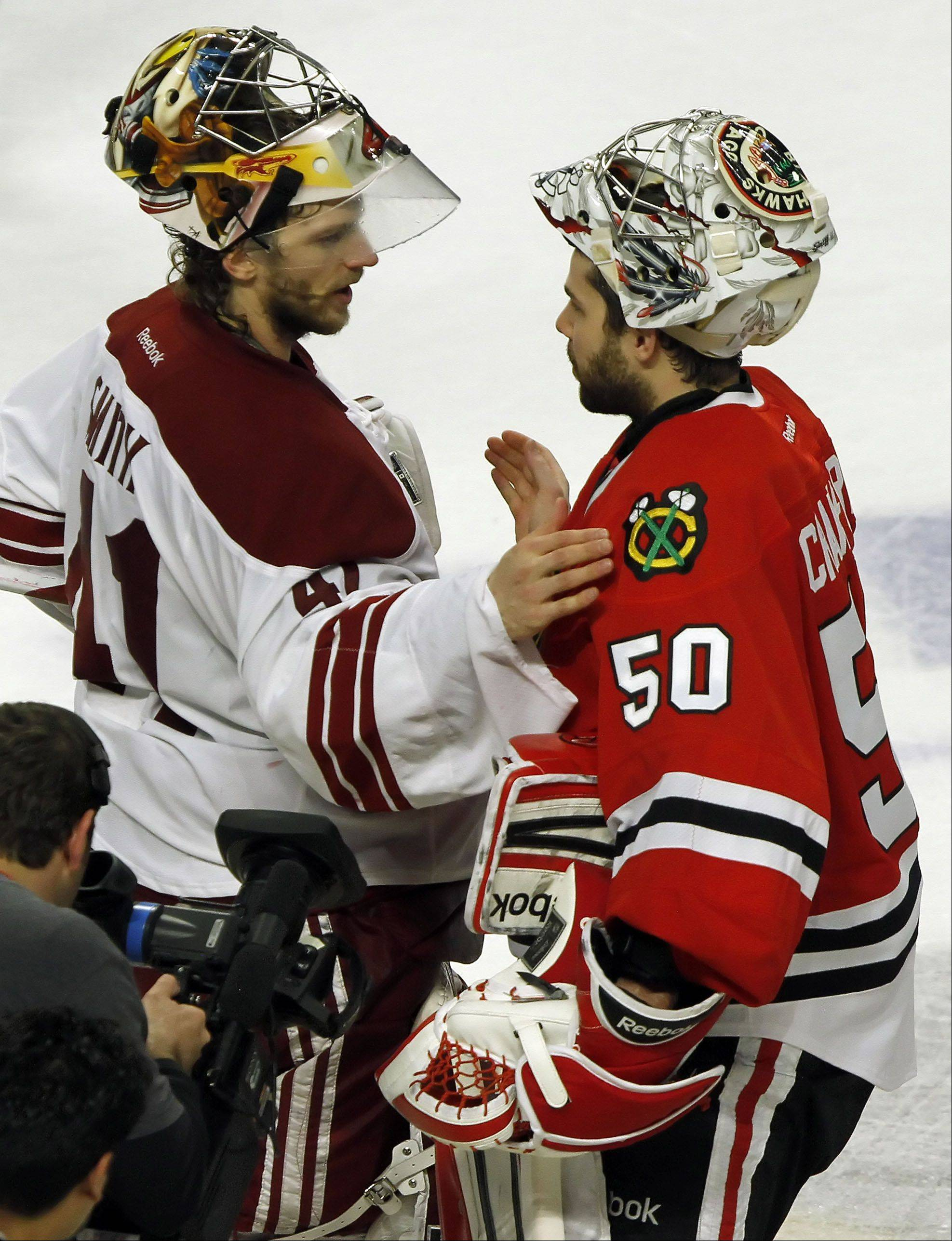 Phoenix Coyotes' goalie Mike Smith and Chicago Blackhawks' goalie Corey Crawford meet at center ice after the game.