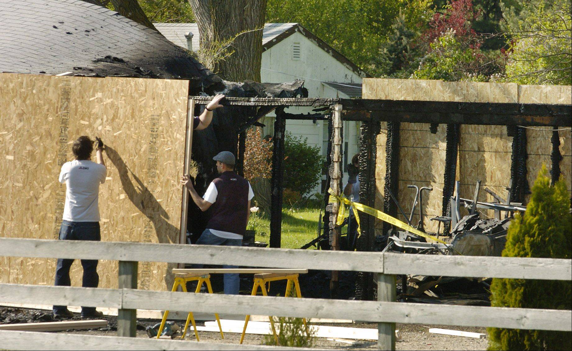 Workers board up the aftermath of a fatal garage fire on North Arlington Heights Road in Long Grove. Authorities believe the home's 46-year-old owner died in the fire.