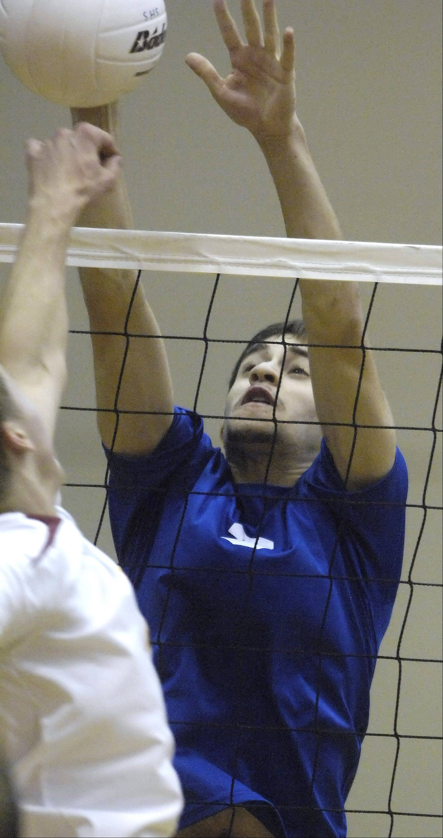 Hoffman Estates' Gabe Alvelo blocks a ball at the net during Tuesday's game against Schaumburg.