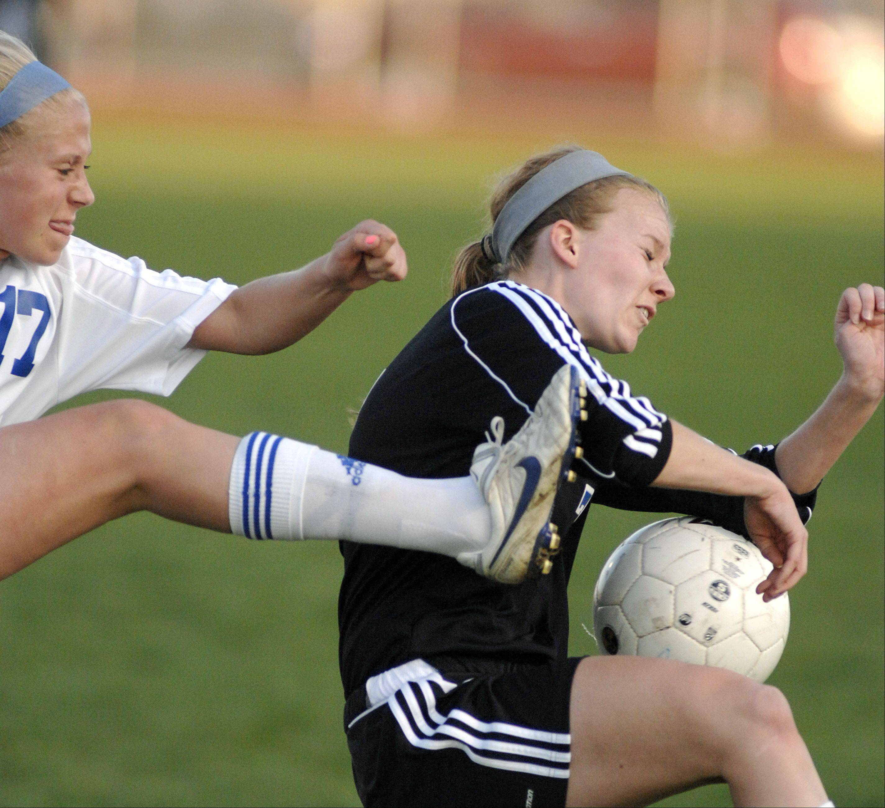 St. Charles North's Kelly Manski and Geneva's Hope Goodman fight for the ball in the first half on Tuesday.