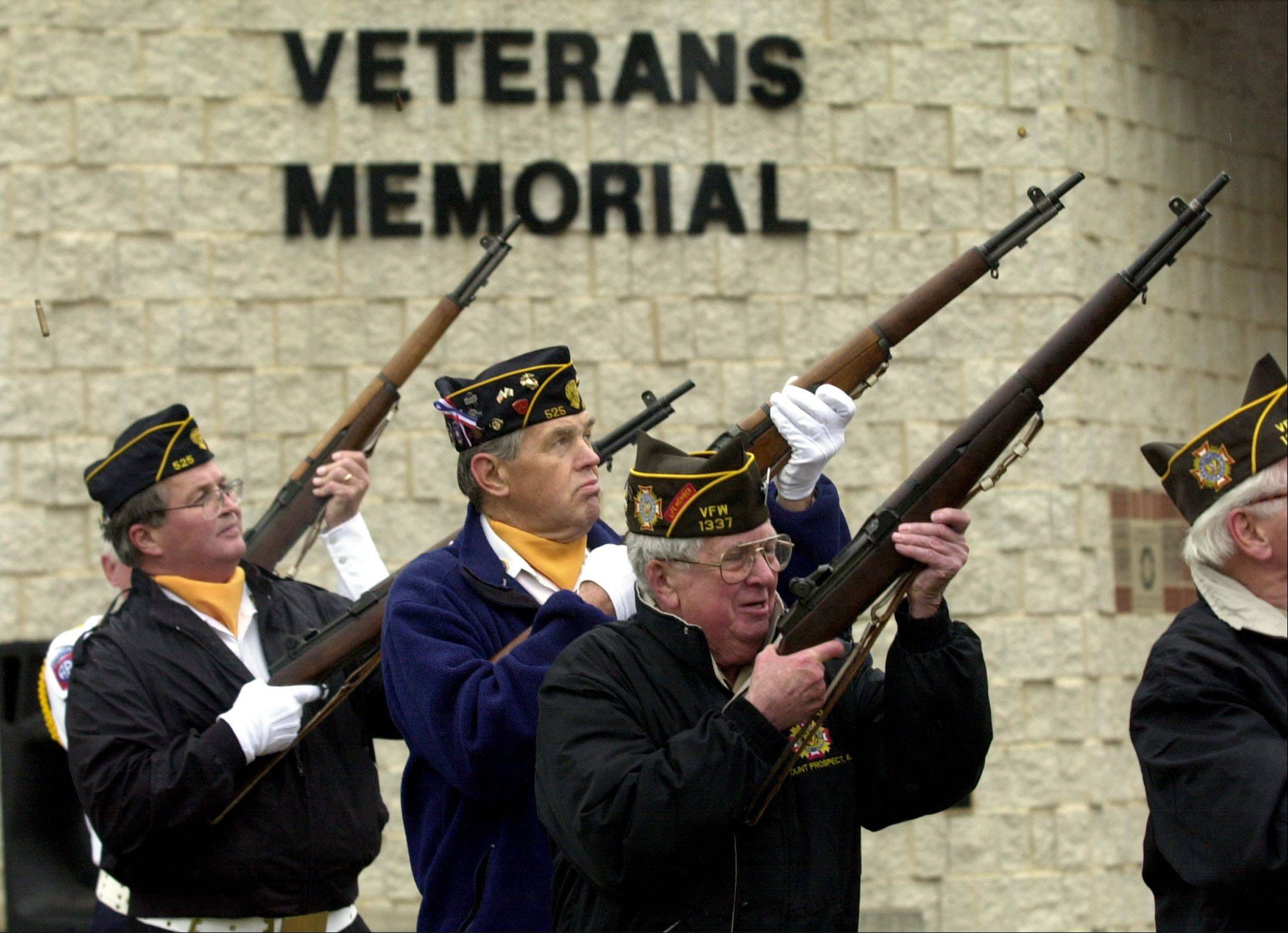 Members of the American Legion Post 525 and VFW Post 1337 give a rifle salute during the Mount Prospect Veterans Day ceremony at the Veterans Memorial Band Shell in Lions Memorial Park.