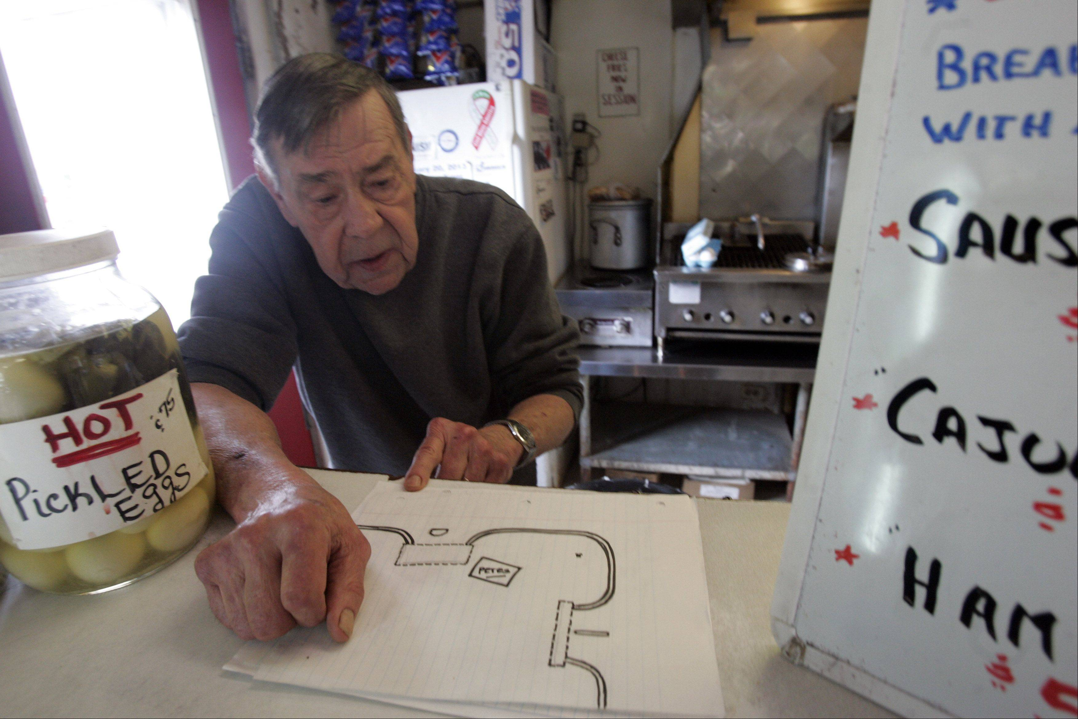 Peter Prevenas, owner of Pete's Famous Hot Dogs and Country Restaurant in Lily Lake, looks over a map he drew that shows how his property, specifically his parking lot, will be changed due to the changes being made at Routes 47 and 64. Customers will only be able to make right turns in and out of his business.