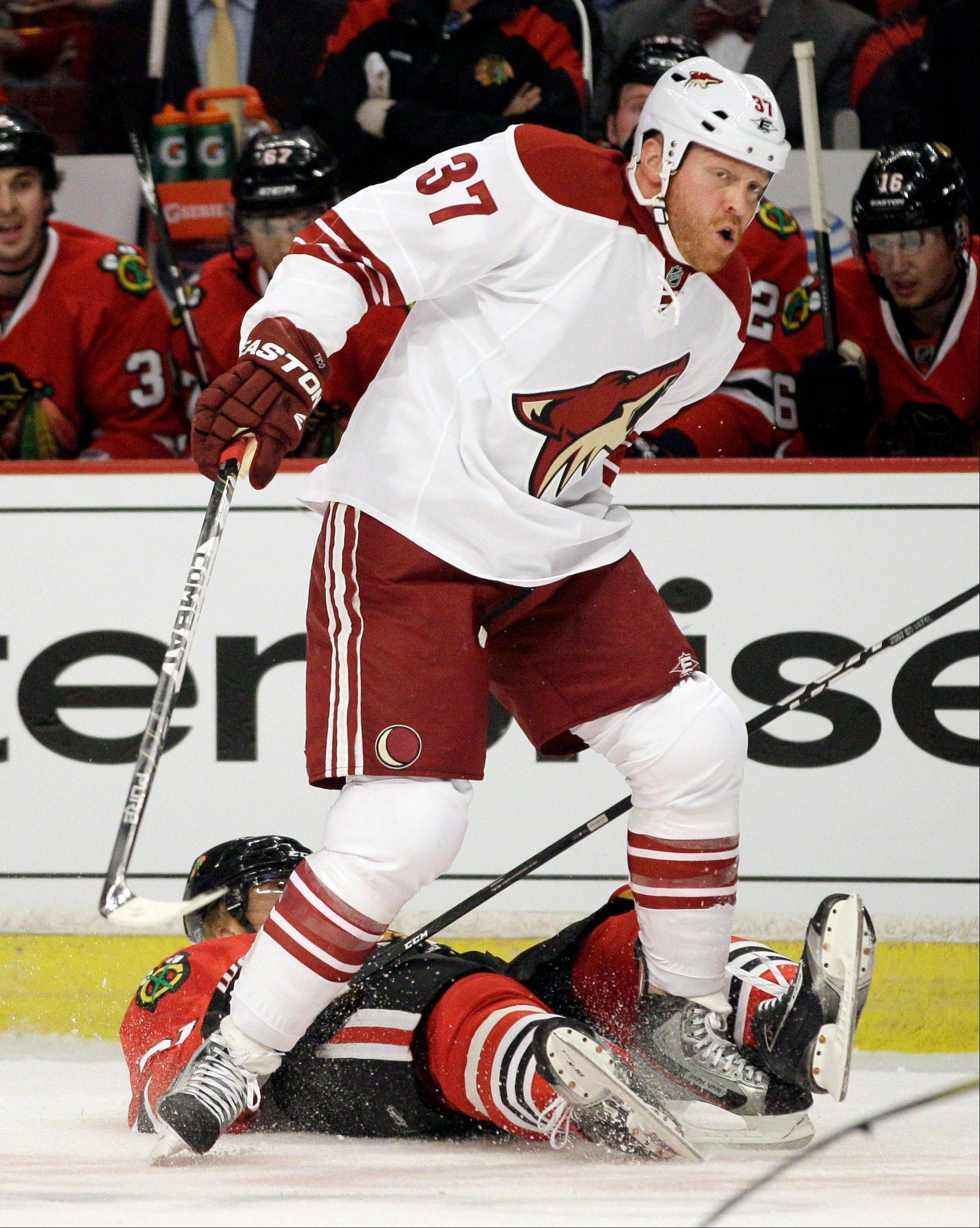 Blackhawks' Marian Hossa (81) of Slovakia, falls down after hit from Phoenix Coyotes' Raffi Torres (37) during the first period of Game 3 of an NHL hockey Stanley Cup first-round playoff series in Chicago, Tuesday, April 17, 2012.