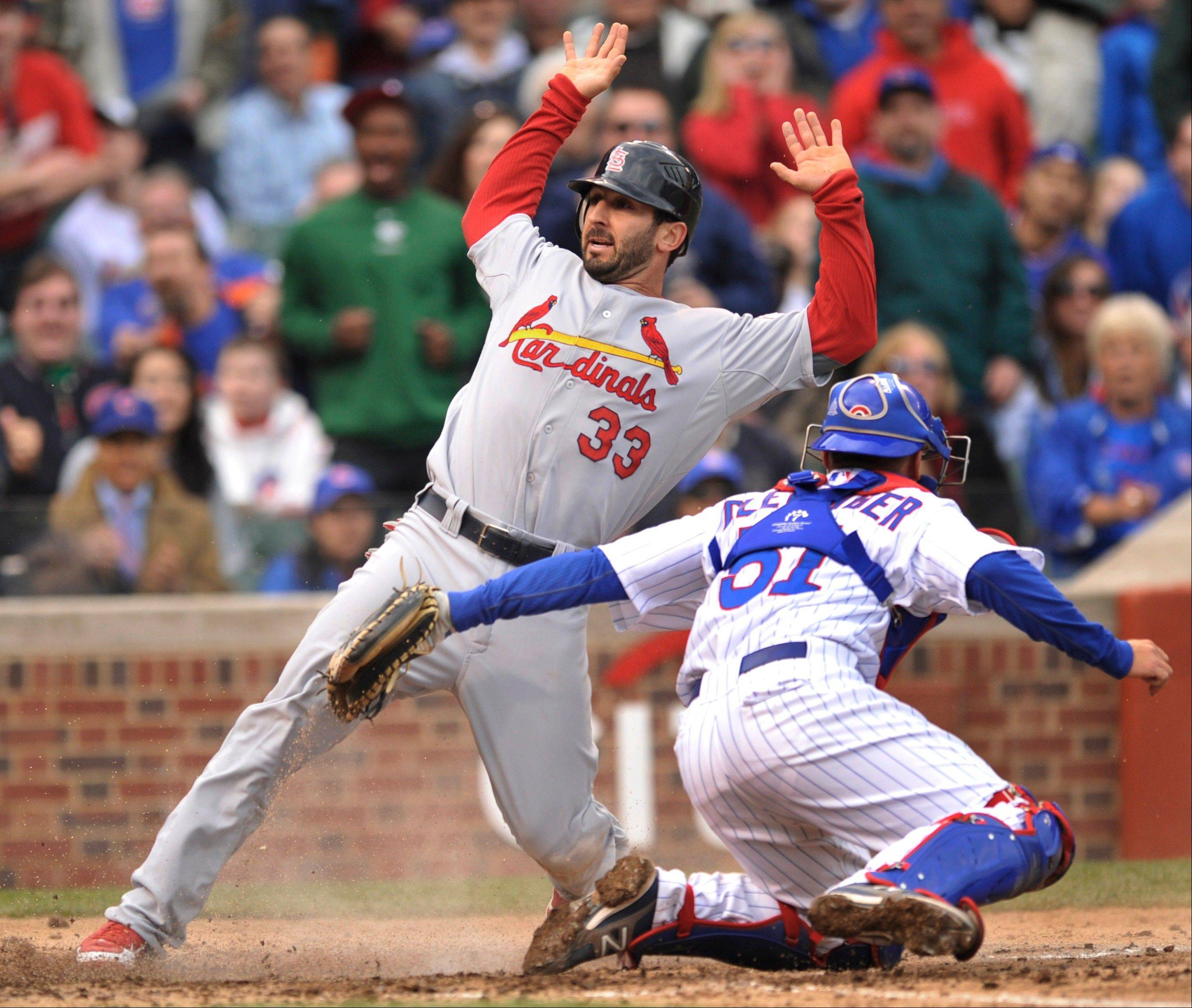 The St. Louis Cardinals' Daniel Descalso scores on a Matt Carpenter single as Cubs catcher Steve Clevenger tries to apply the tag Wednesday during the third inning.