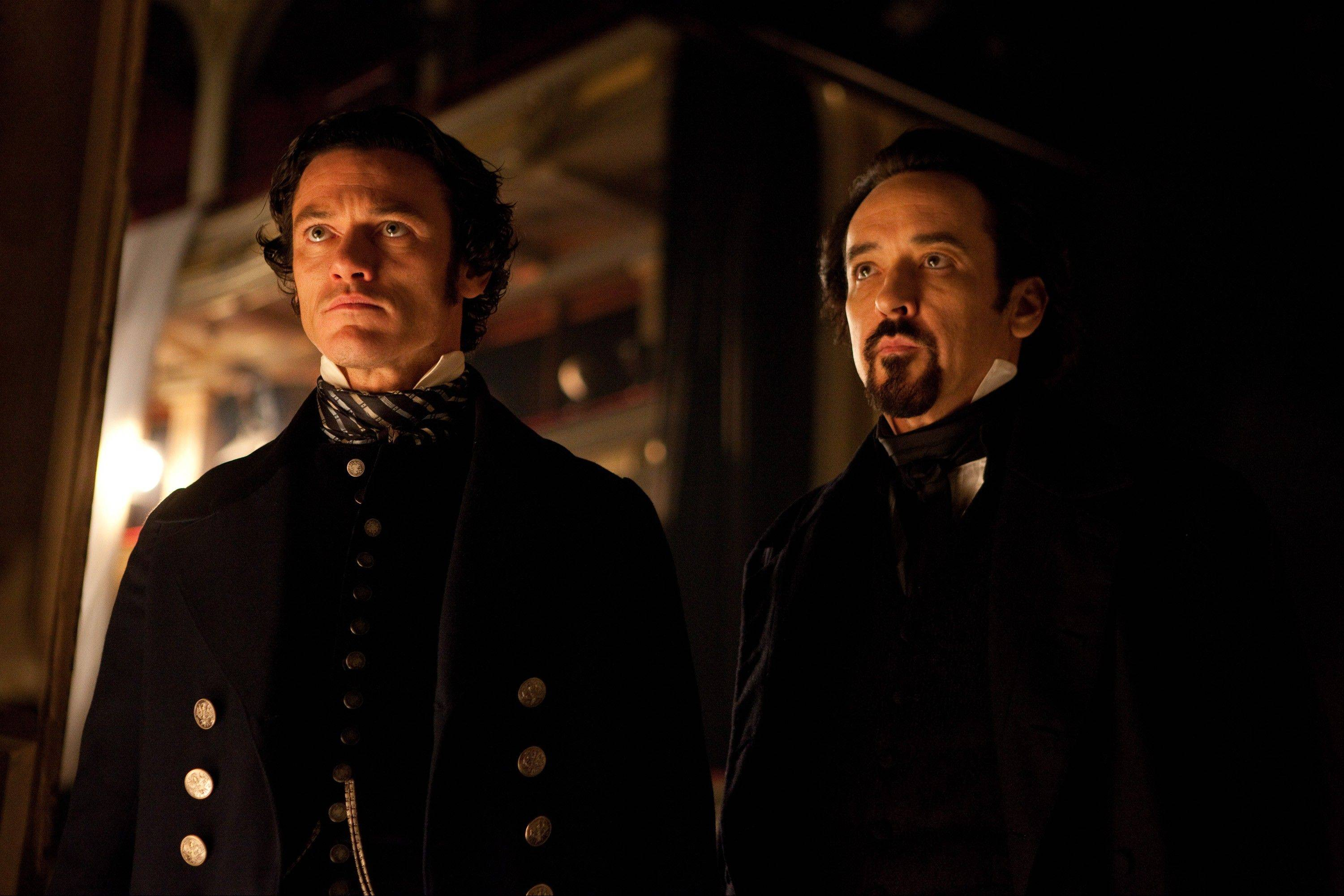 "Baltimore police detective Fields (Luke Evans), left, and Edgar Allan Poe (John Cusack) team up to stop a diabolical serial killer in the period thriller ""The Raven."""