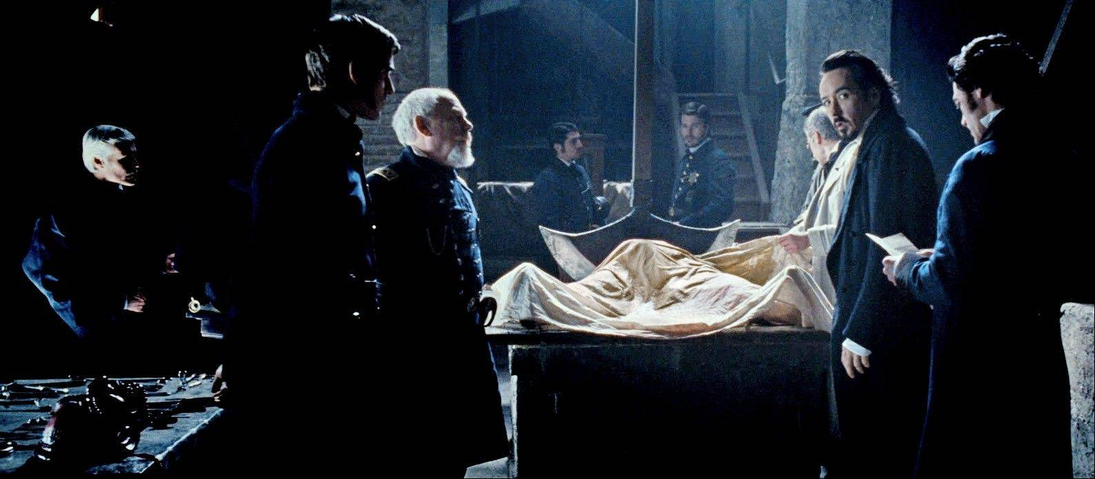Edgar Allan Poe (John Cusack), right, examines a crime scene involving a device from his literary creation.