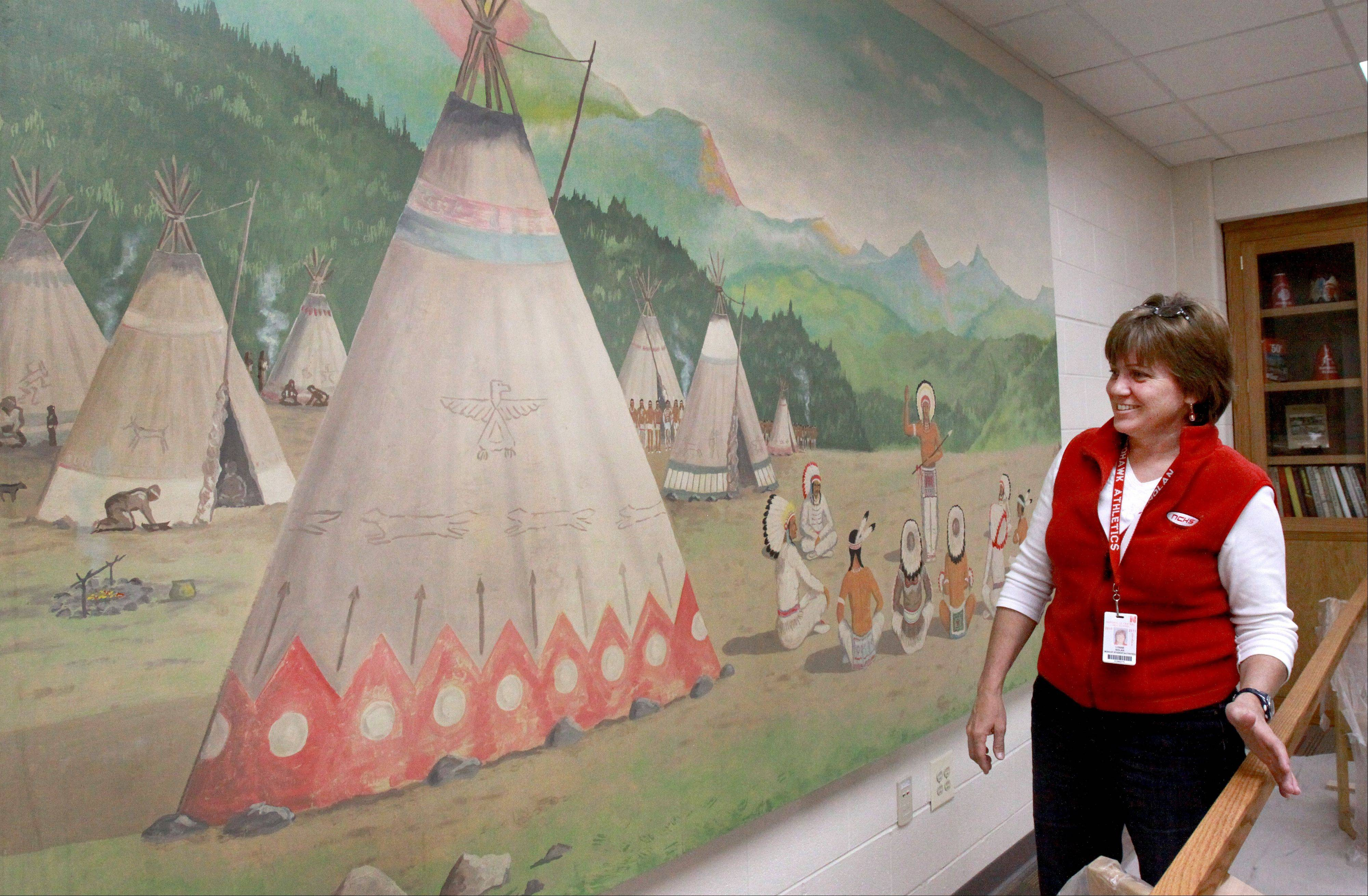 Lynne Nolan, dean of student activities at Naperville Central High School, checks out a canvas mural that was rescued from the school's basement bathroom and has been restored.