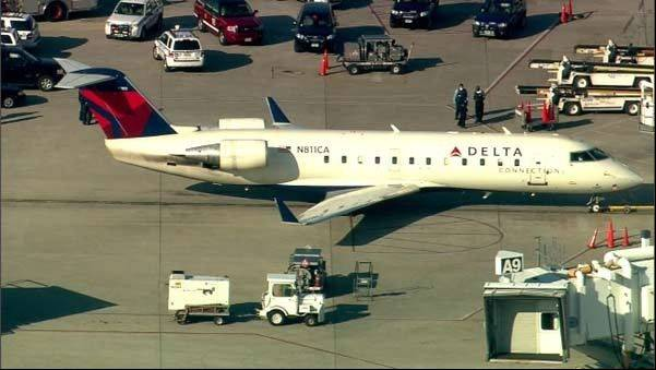 This photo from video shows fire and ambulance crews on the runway at Midway Airport while a Delta flight was quarantined for about three hours Thursday in Chicago.