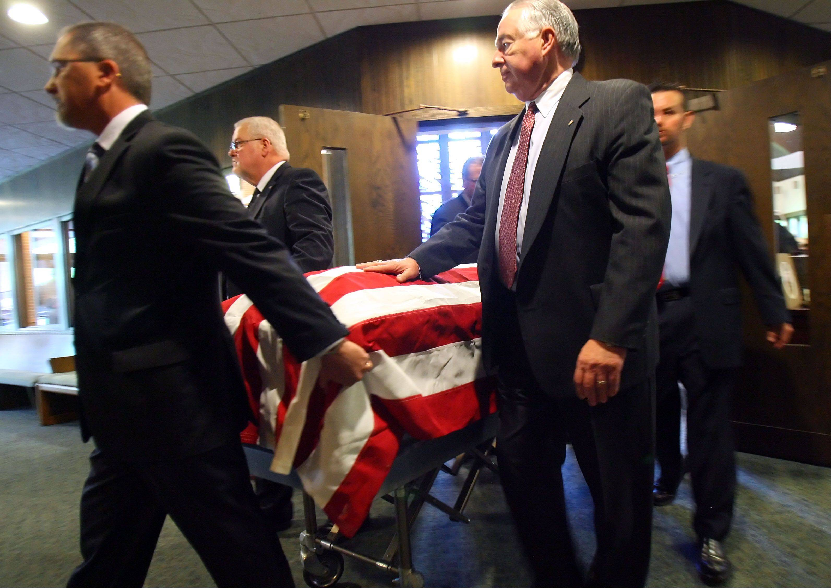 Pallbearers wheel out the flag-draped casket of Spencer Loomis during his funeral Thursday at St. Peter United Church of Christ in Lake Zurich.