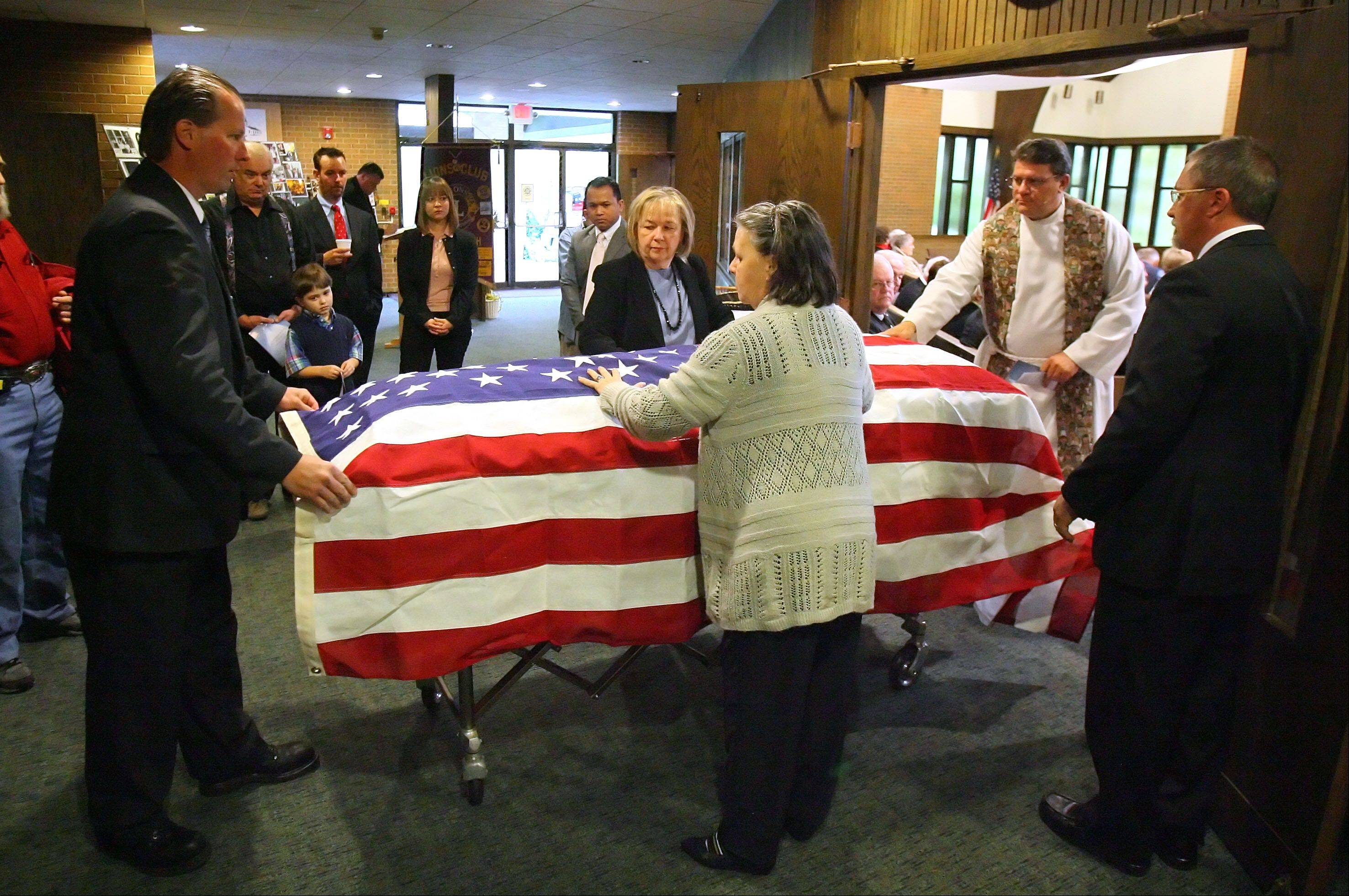 Peggy Loomis Spencer of Leander, Texas and Nancy Loomis Schroeder of Ingleside, middle, spread the American flag over the casket of their father Spencer Loomis during his funeral Thursday at St. Peter United Church of Christ in Lake Zurich.