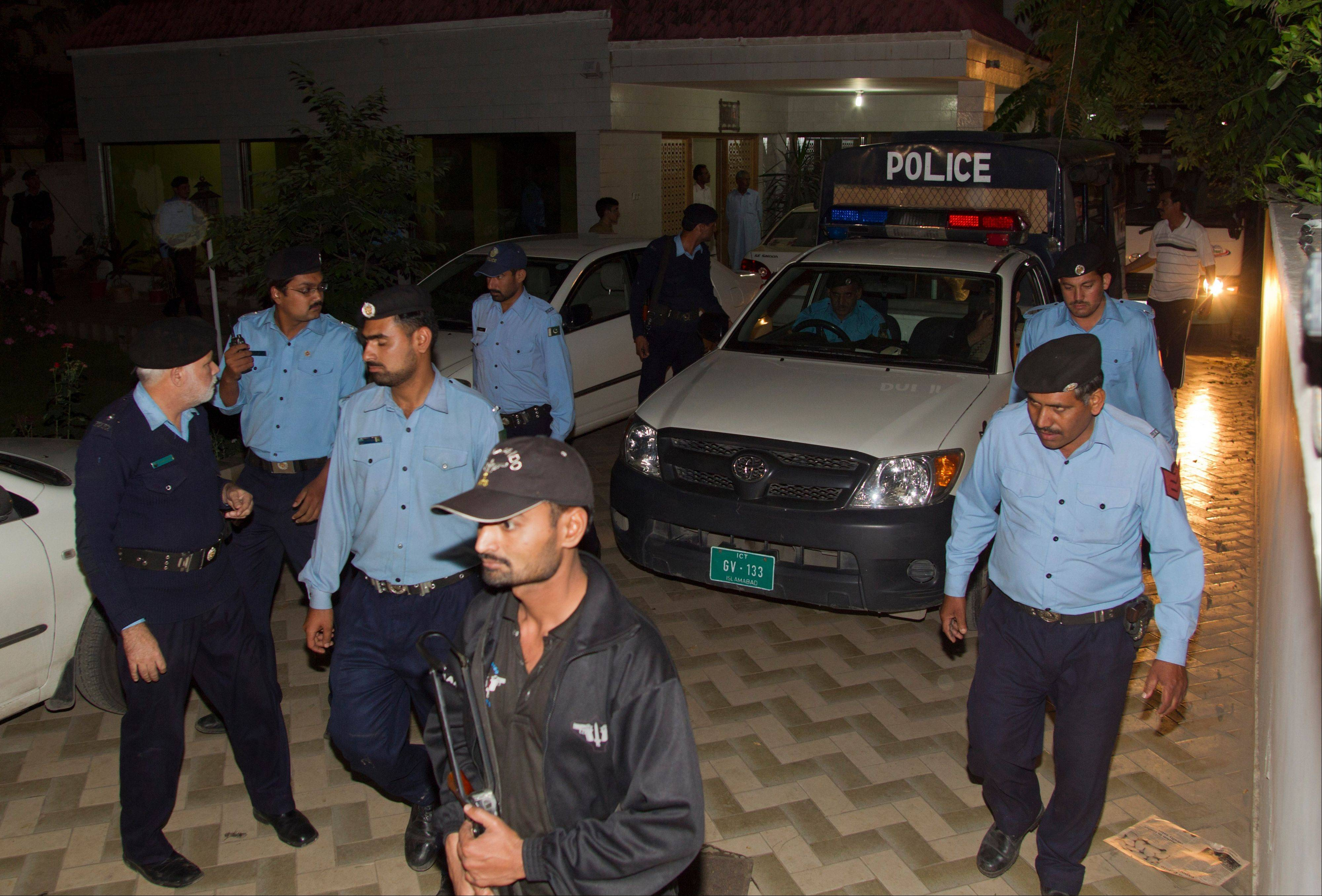 Police officers escort a vehicle carrying the family of Osama bin Laden Thursday in Islamabad, Pakistan. A van carrying the three widows and children of Bin Laden has left the house where they have been staying in Islamabad and is en route to the airport, from where they will be deported to Saudi Arabia, officials and witness said.