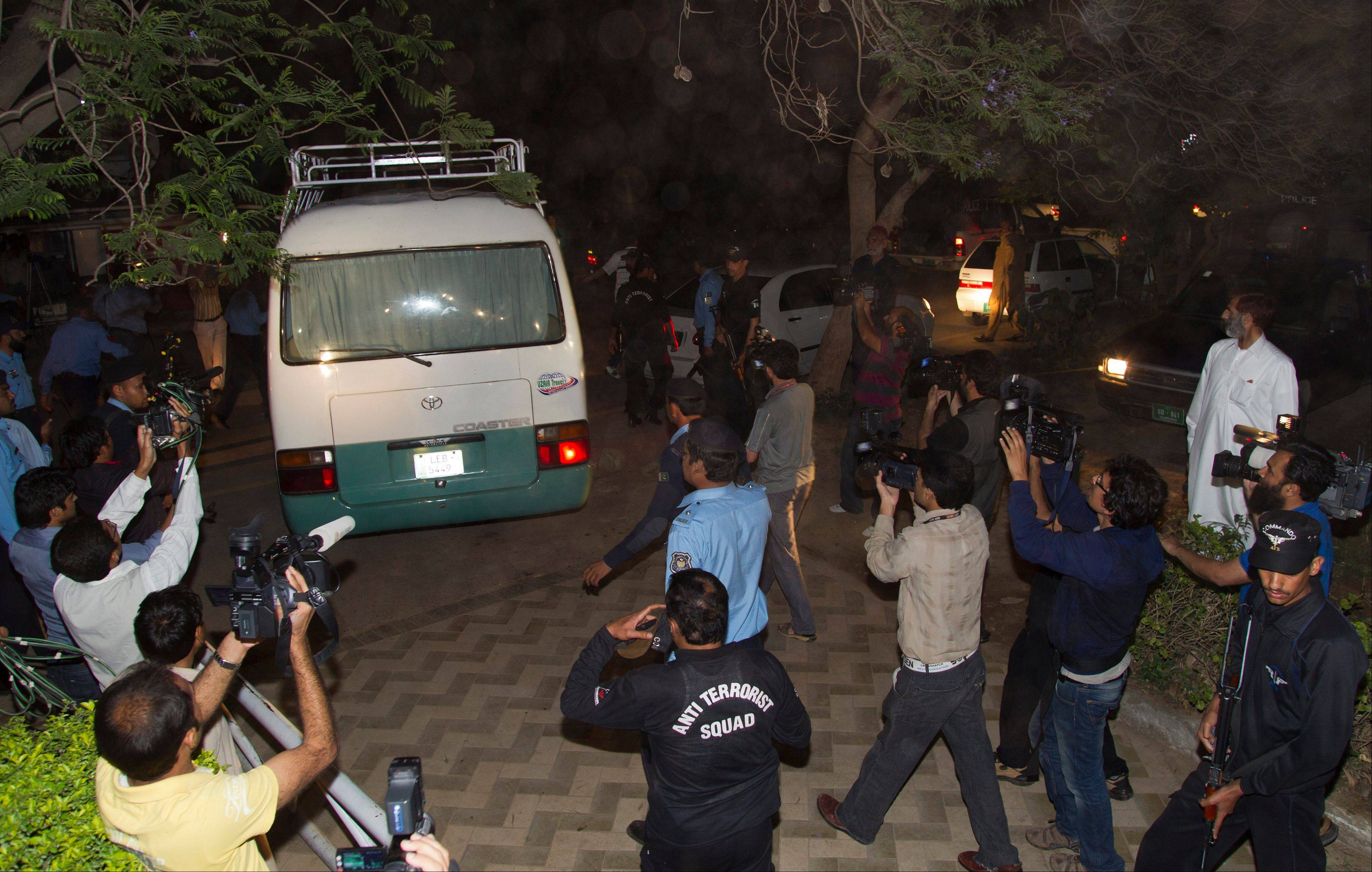 Media chase a minivan carrying the family of Osama bin Laden in Islamabad, Pakistan on Thursday.