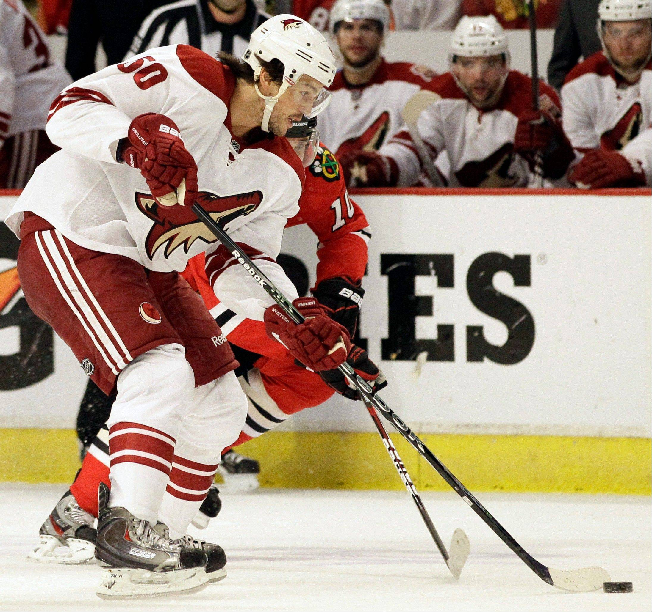 Phoenix Coyotes' Antoine Vermette (50) controls the puck against Chicago Blackhawks' Patrick Sharp (10) during the first period of Game 6 of an NHL hockey Stanley Cup first-round playoff series in Chicago, Monday, April 23, 2012.